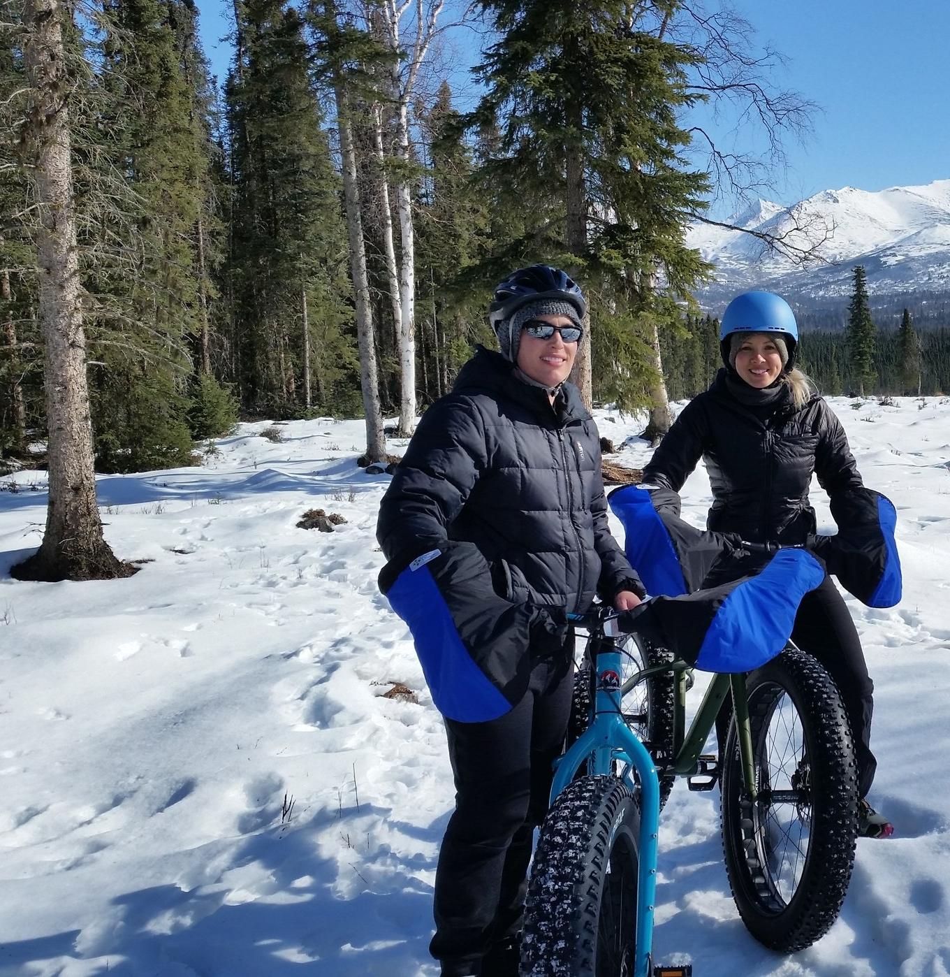 Happy couple fat tire biking on sunny winter day
