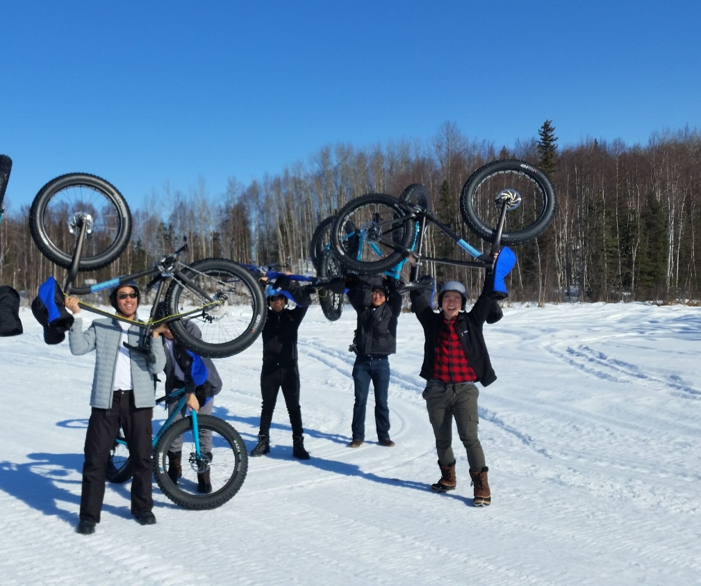 Group of guys raise their fat tire bikes overhead after winter bike tour