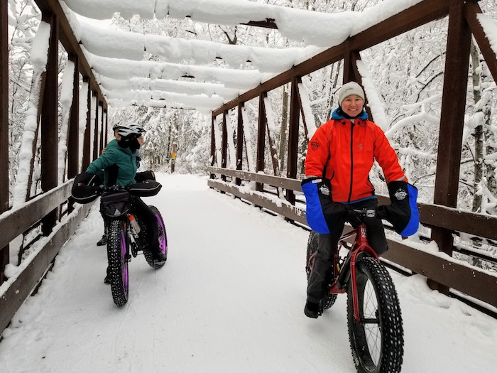 Group rides over bridge in Campbell Creek winter