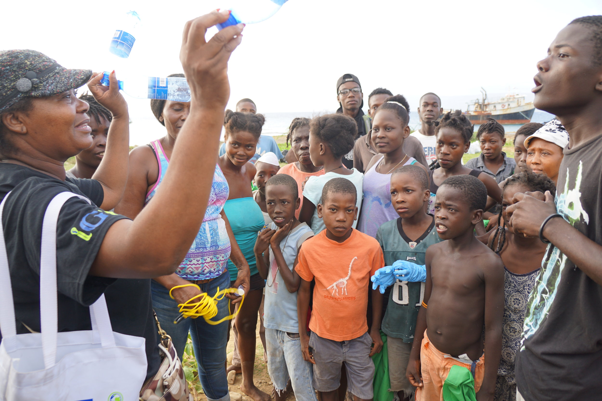 "Vice President of International Affairs, Lubernia ""Mama Betty"" Nelson , educates the children of Port de Paix on the importance of keeping plastics out of the bodies of water."