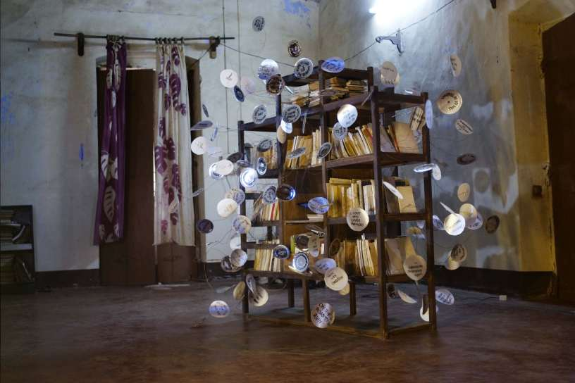 Text Sculpture  (2017), mixed-media installation including book shelf, books, wires, paper plates etc. Image courtesy: the artist.