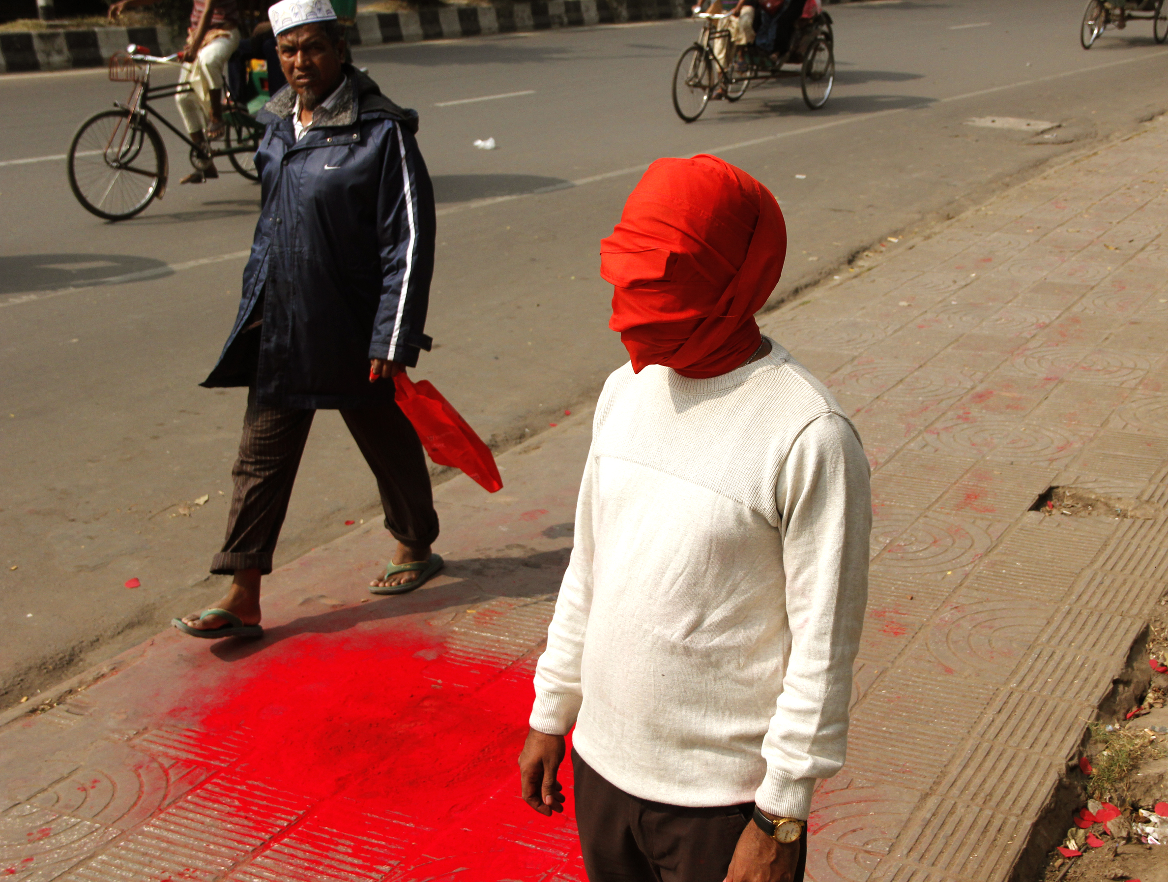 "Red Dot on a Red Road  (2017), still from live performance as part of D'LAB (Dhaka Live Art Biennale) at Dhaka University Campus.  Courtesy of the artist. Photo credit: Imtiaz-al-Tareq.           Normal     0                     false     false     false         EN-GB     X-NONE     HI                                                                                                                                                                                                                                                                                                                                                                                                                                                                                                                                                                                                                                                                                                                                                                                                                                                                                                                                                                                                                                                                                                                                                                                                                                                                                                                                                                                                                                                                                                                                                                                                                                                                                                     /* Style Definitions */  table.MsoNormalTable 	{mso-style-name:""Table Normal""; 	mso-tstyle-rowband-size:0; 	mso-tstyle-colband-size:0; 	mso-style-noshow:yes; 	mso-style-priority:99; 	mso-style-parent:""""; 	mso-padding-alt:0in 5.4pt 0in 5.4pt; 	mso-para-margin-top:0in; 	mso-para-margin-right:0in; 	mso-para-margin-bottom:10.0pt; 	mso-para-margin-left:0in; 	line-height:115%; 	mso-pagination:widow-orphan; 	font-size:11.0pt; 	mso-bidi-font-size:10.0pt; 	font-family:""Calibri"",sans-serif; 	mso-ascii-font-family:Calibri; 	mso-ascii-theme-font:minor-latin; 	mso-hansi-font-family:Calibri; 	mso-hansi-theme-font:minor-latin; 	mso-bidi-font-family:Mangal; 	mso-bidi-theme-font:minor-bidi; 	mso-fareast-language:EN-US; 	mso-bidi-language:HI;}"