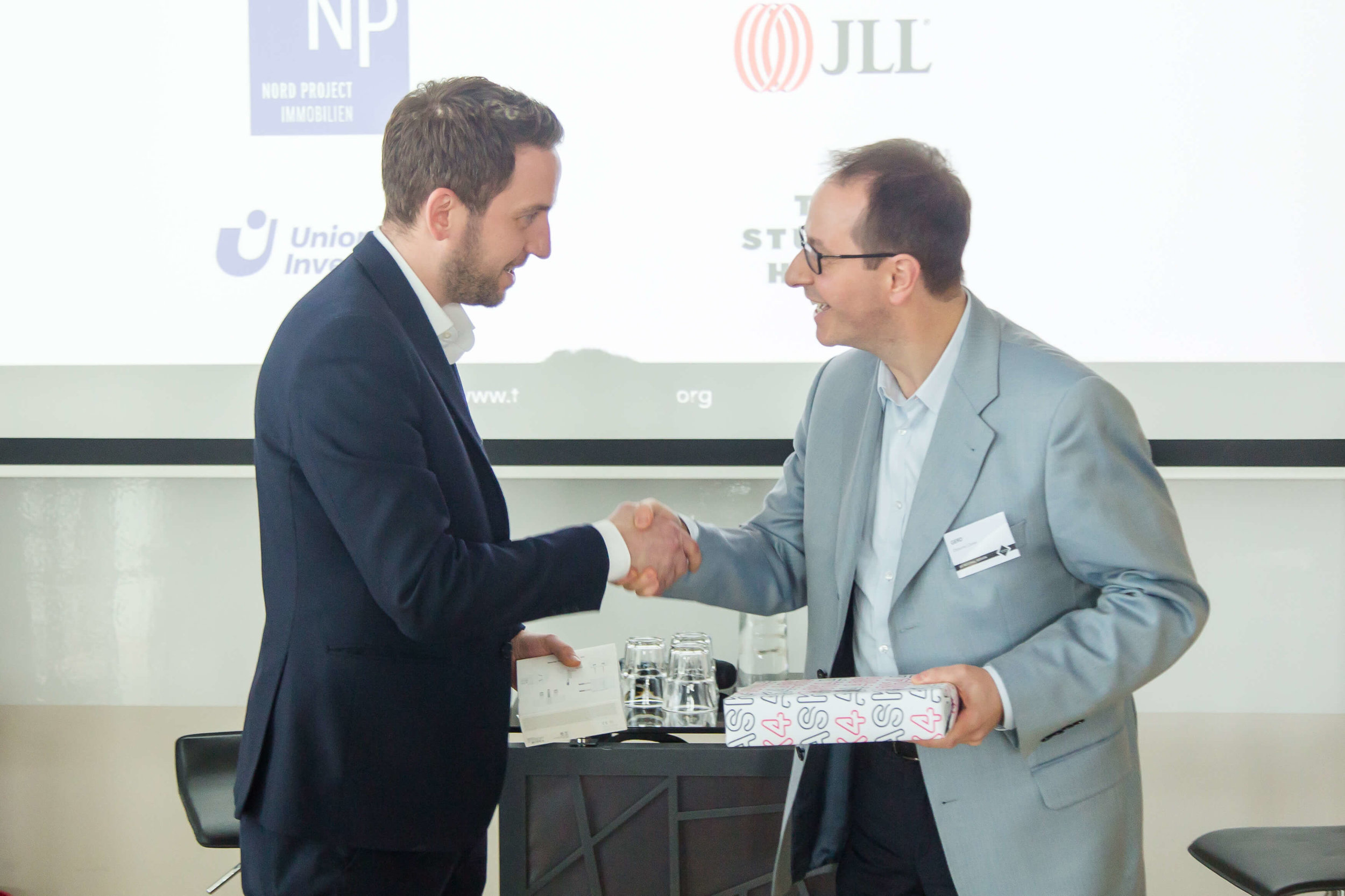 Billy Kontoulis from ASK4 presents the iPad to Gerd Hoor from Osborne Clarke.