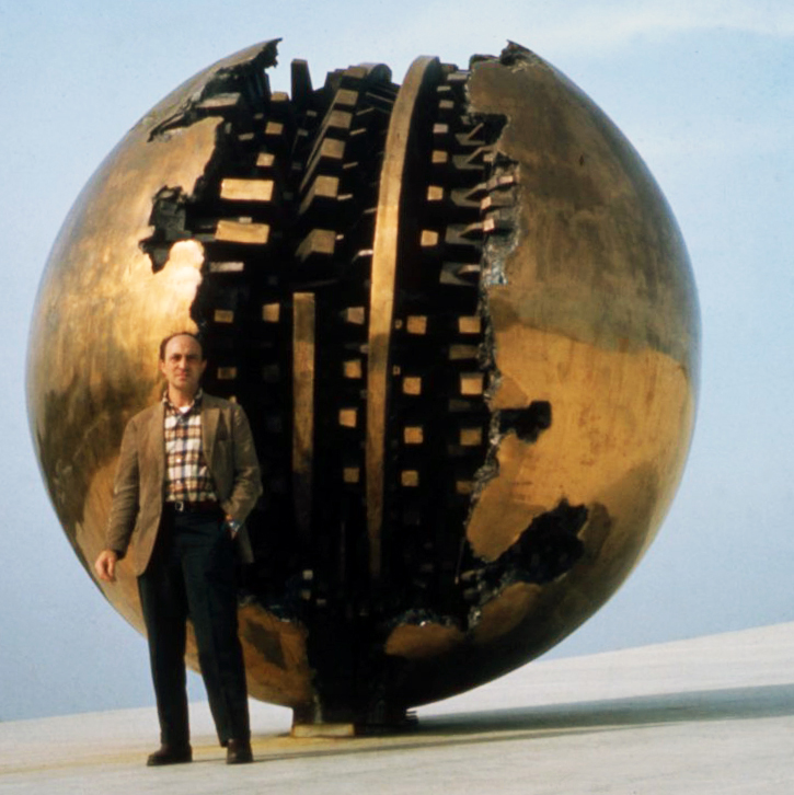 "Arnaldo Pomodoro in front of ""Sfera grande,"" 1966-67 (bronze ø 350 cm) installed on the roof of the Italian Pavilion at the Montreal Expo, 1967. Photograph Ugo Mulas © Eredi Mulas. All rights reserved."
