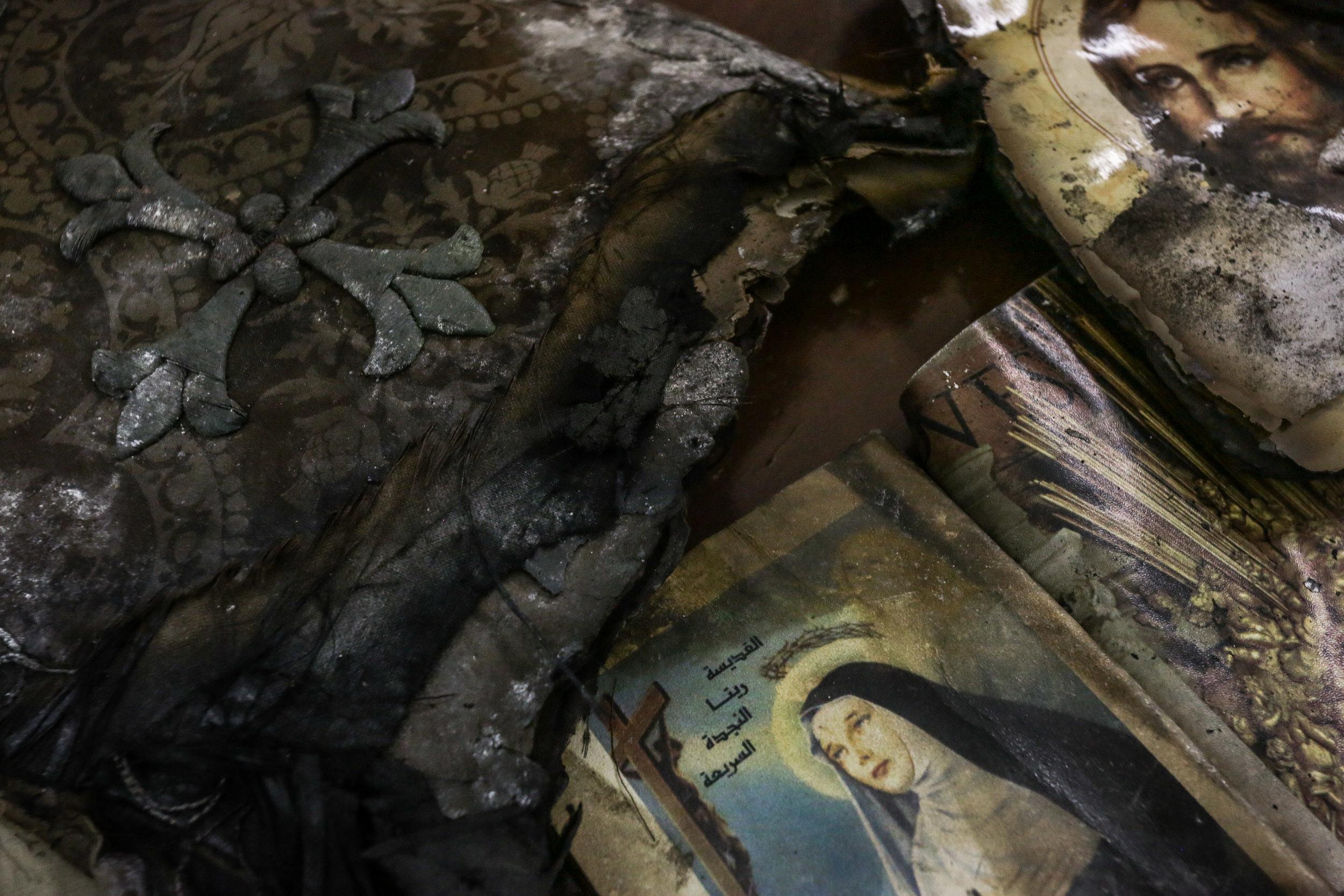 Egypte Azyut 03 septembre, 2013-- Les restes de livres brulés dans l'église Jésuite de Sainte Thérèse à Azyut en Haute Égypte. Le 14 août 2013, des partisans du président déchu Mohamed Morsi, issu des Frères musulmans, sont dispersés dans la violence au Caire. Les affrontements font des centaines de morts. La réplique est instantanée. Une vague de violence s'abat sur les communautés coptes du pays, des Chrétiens qui représentent environ 10 pour cent de la population égyptienne. Selon Amnesty International, plus de 200 écoles, commerces et maisons appartenant à des chrétiens sont attaqués. Une soixantaine d'églises et d'institutions coptes sont sérieusement endommagées. Au moins quatre personnes sont tuées. Voir Les  Coptes