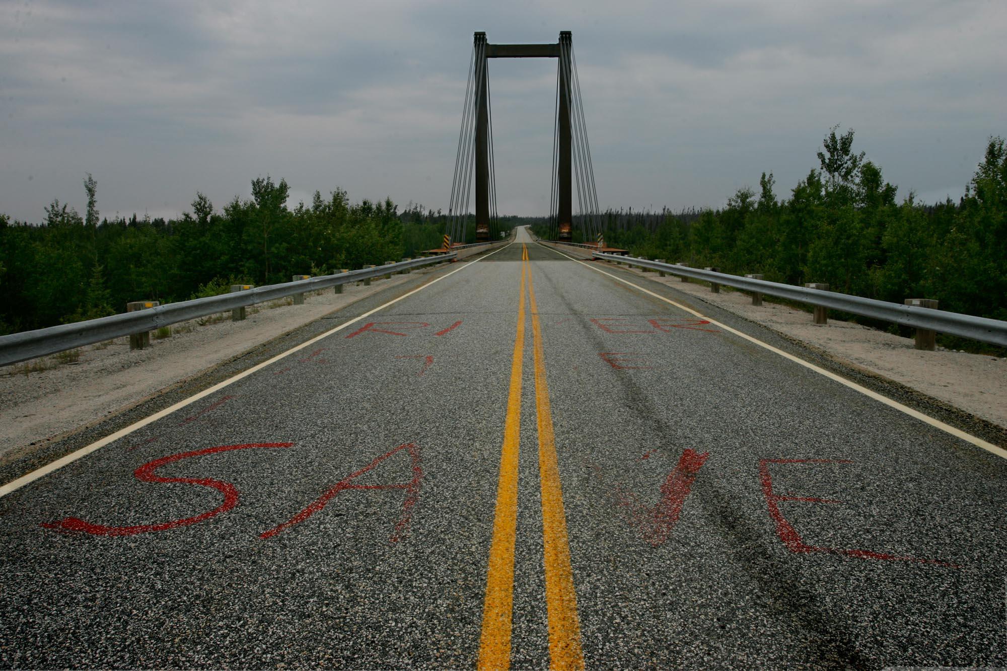 Rivière Rupert, Juillet 2006. Le pont qui enjambe la Rivière Rupert  sur la route de la Baie James au rapide Oatmeal est couvert de message messages sans équivoque. Ici sur le bitume on a peint en lettres rouges, Save The River