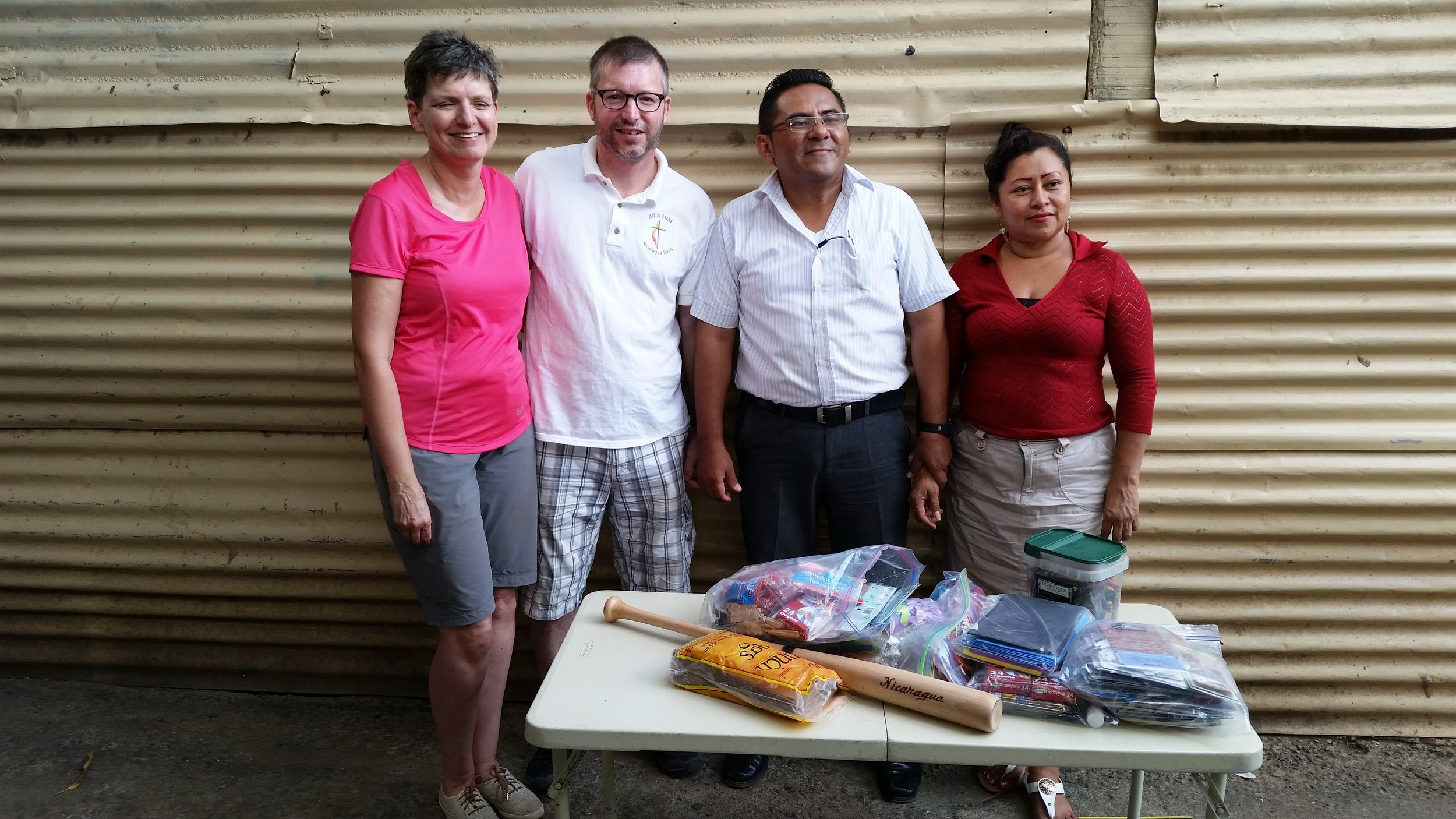 P  astor Ian and Gwenna pose with Pastor Wilmer and his wife with some items we donated to their school today.