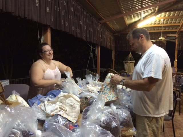 Sarah and Dragos share a joke while packing food bags.