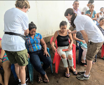 Barbara (standing left) and Heather (standing right) pray for two female patients at Manolo Morales hospital.