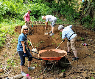 Sue steadies the wheelbarrow while Barbara, Conrad and Laura filler-up!