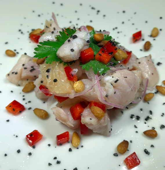 CEVICHE - Small tropical fin fish (usually snapper) diced and cured in lime juice, Mixed with grapefruit sections, red onion, cilantro and red bell pepper. Topped with paprika toasted pine nuts and black Hawaiian sea salt