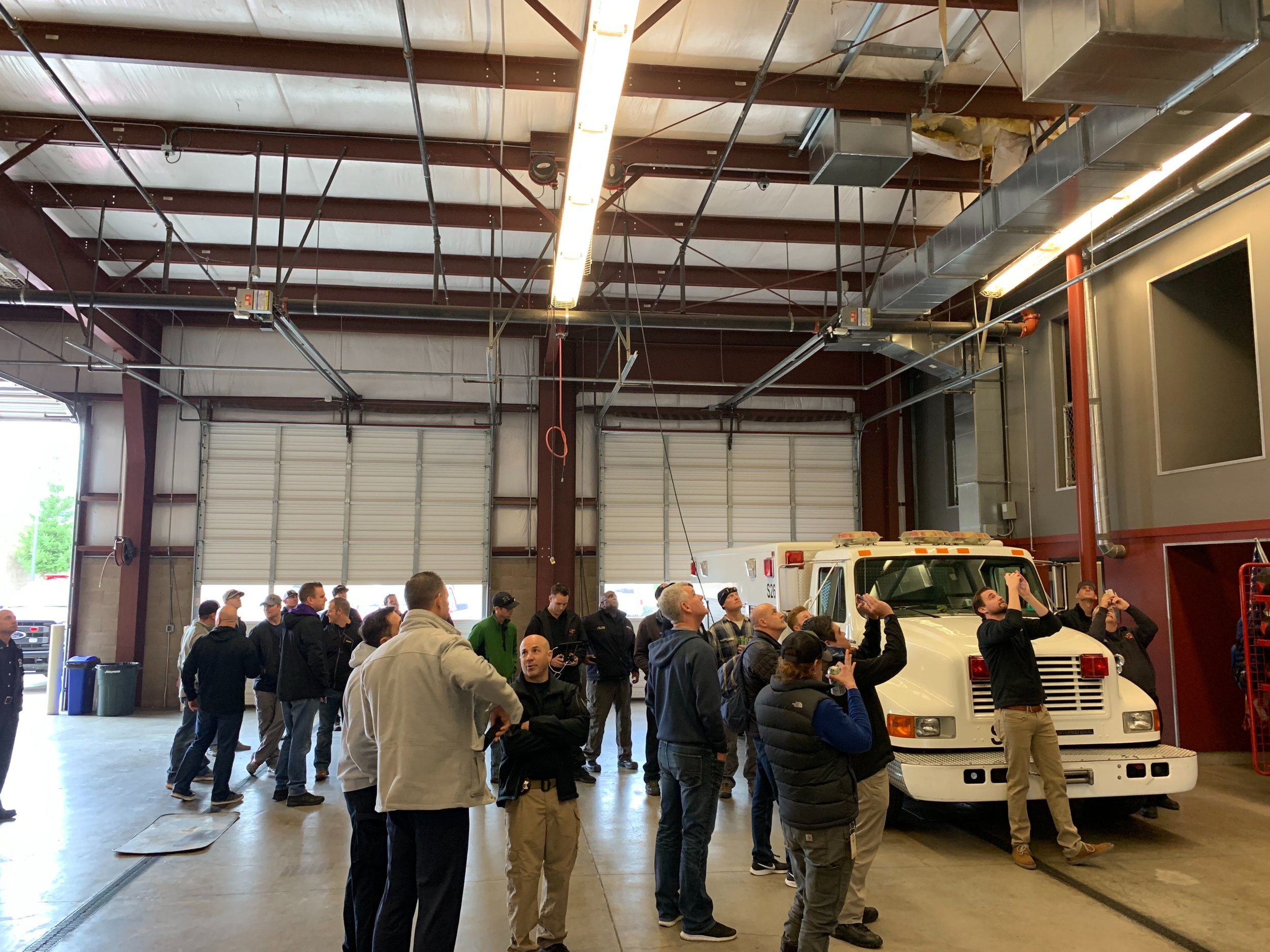 Firefighters in a firehouse with large white truck.jpg