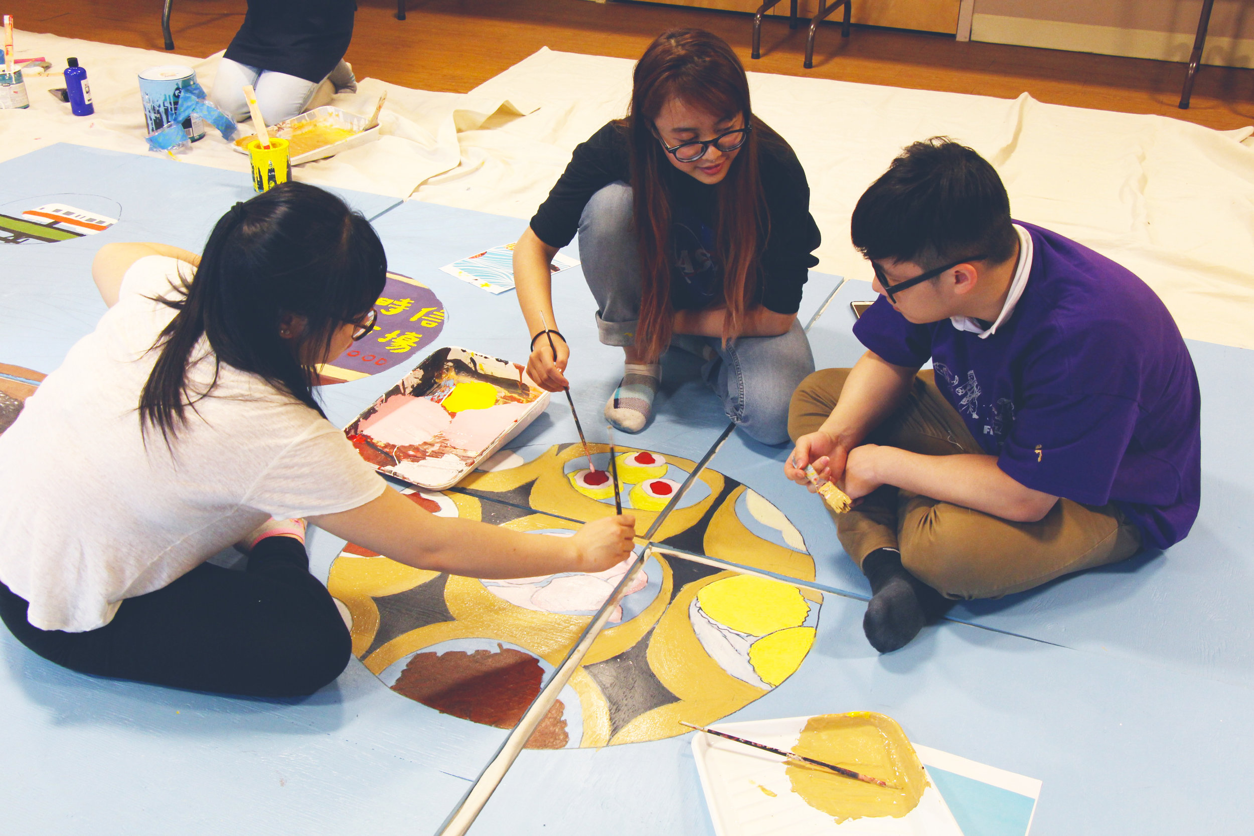 Youth artists painting the 2017 ThinkChinatown Project, a mural currently on display on the facade of 15-25 Harrison Avenue.