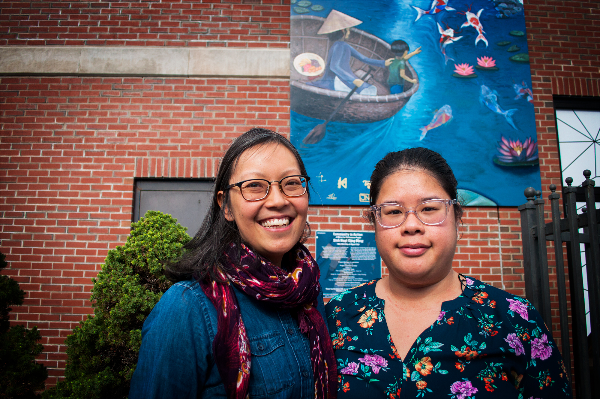 Amy (left) pictured with Carro, a former A-VOYCE youth from 10 years ago, in front of the new community mural in Dorchester's Fields Corner.