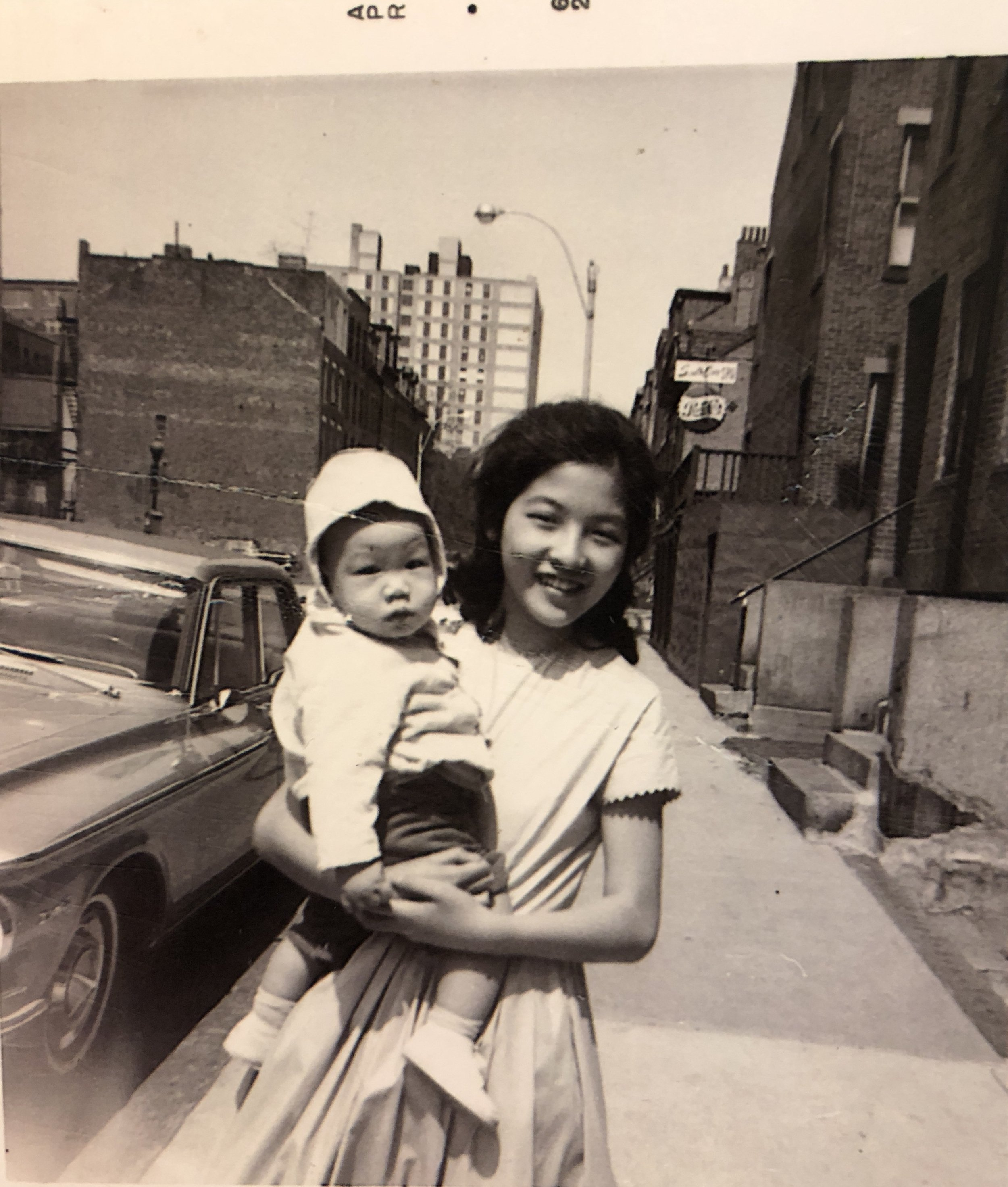 Last Easter Sunday, April, 1962, before the demolition of Hudson Street; Cynthia Yee wearing a polished cotton lilac dress she designed and sewed, babysitting her friend Susan's little brother, Ken Lim.