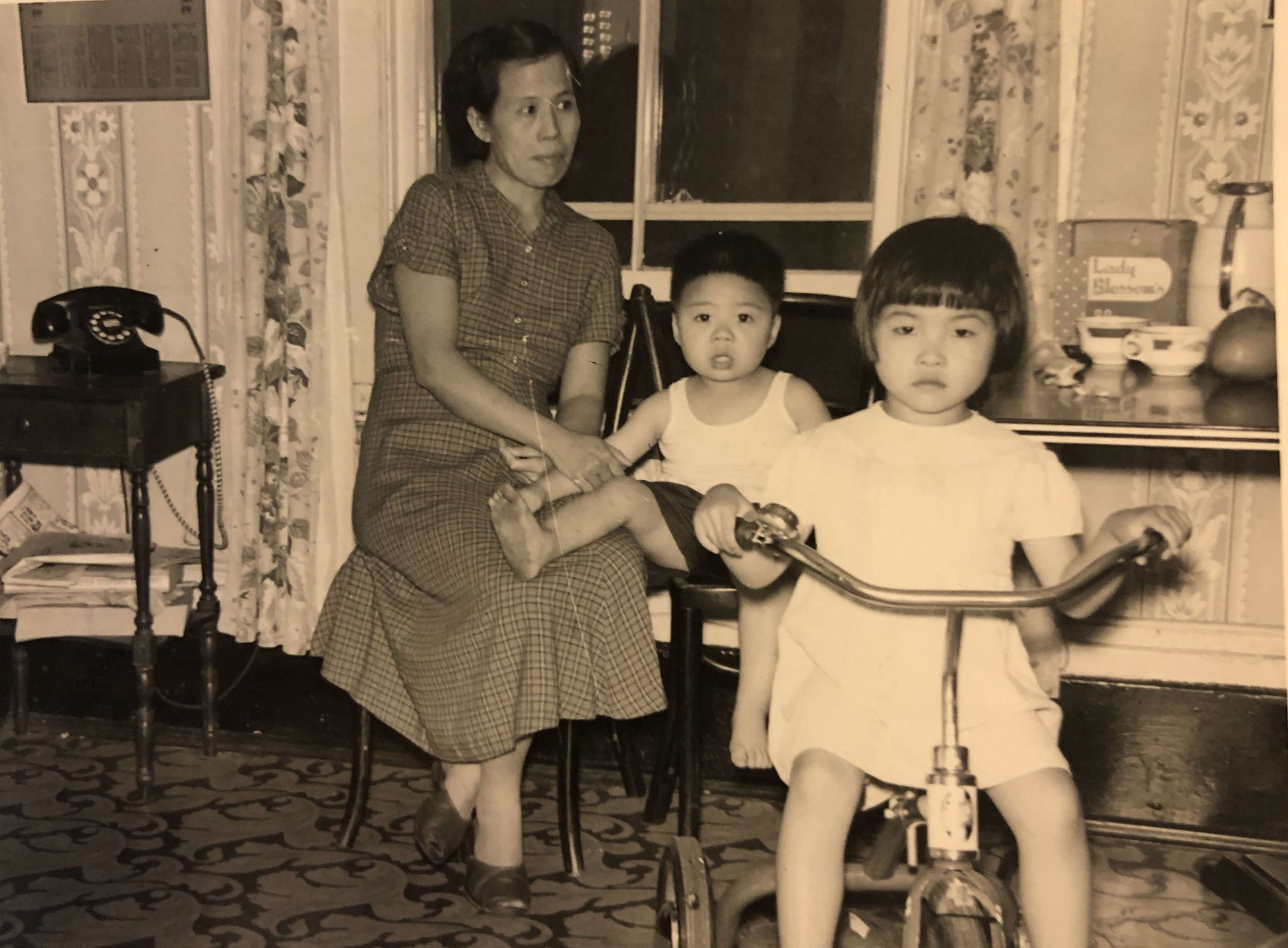Cynthia on a tricycle with her cousin Albert and her mother May Soon Yee inside her home on the second floor of 116 Hudson Street, 1950's