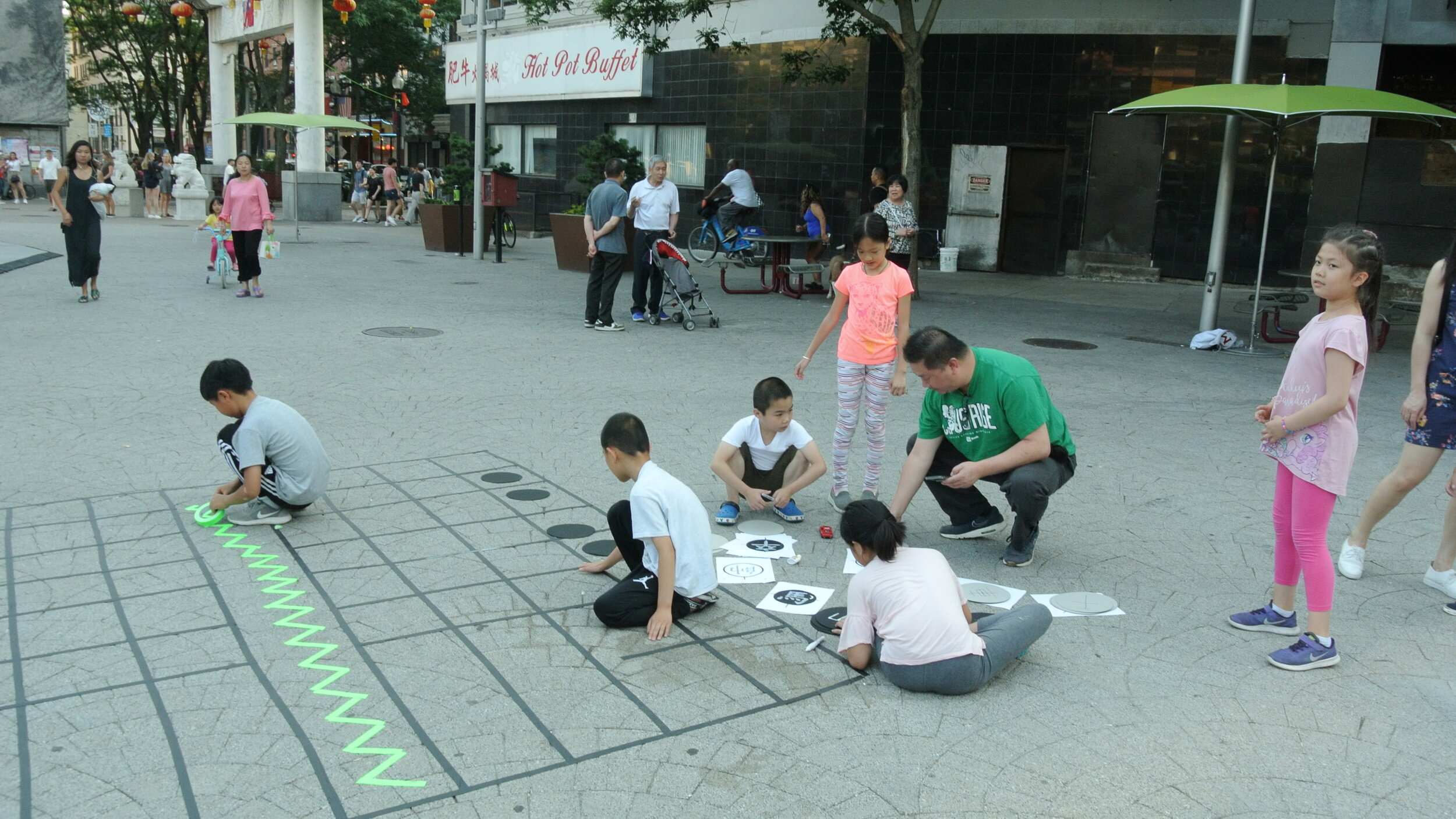 """Ponnapa's Residence Lab installation, """"Sampan"""", mock up in Chin Park, working with Chinatown residents Warren, Henry (not pictured) and local children to test the layout. In Thai, sampan means a connection. Photo courtesy of the artist."""