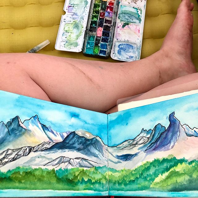 "Have paper, will paint anywhere.  Perched on the side of a mountain, on a rock next to a lake, in a tent, in a snow covered meadow, next to the campfire, in the car while you drive.  I think that's what I love most about what I do. I'm not a ""sit in the studio and paint"" exclusively kind of artist, though I do that for important pieces when I need the elements to stand still. I want to go and do and see all the things and paint it all, even if that makes it harder or my work messy and imperfect most of the time.  When I first started painting I found @drawntohighplaces and fell instantly in love with everything she was and what she was doing. She's the one who taught me that mountains don't have to be brown. I'm still in awe of her and her travels, the way she can paint large pieces on the top of a mountain in the middle of winter, her style, her as a person. She just got married on top of a peak in the north cascades and had to traverse a glacier to get there for the love of god.  She introduced me to @christinamckeownart and through them I found @Rachel.pohl @sarahvirginiauhl @paintthemountain and a bunch of other amazing artists who were doing amazing things and creating art outside.  As my goals for myself as an artist change and evolve, as they should, one things seems to remain constant: I want to climb, paddle and snowboard everything that I can and I want to paint as I go.  There's no other word to use other than content to describe how I felt sitting in a tent next @caitlinlanier a few weeks ago as she read and I painted, the sound of rain pouring down and thunder cracking around us. We had been lounging on a nice rock with a stellar view of the Sawtooths next to Hell Roaring lake moments before, but a sudden summer storm chased us in. In that moment, In the tent and next to my good friend, covered in dirt and paint and a little damp, I felt both deeply at peace and brilliantly alive."