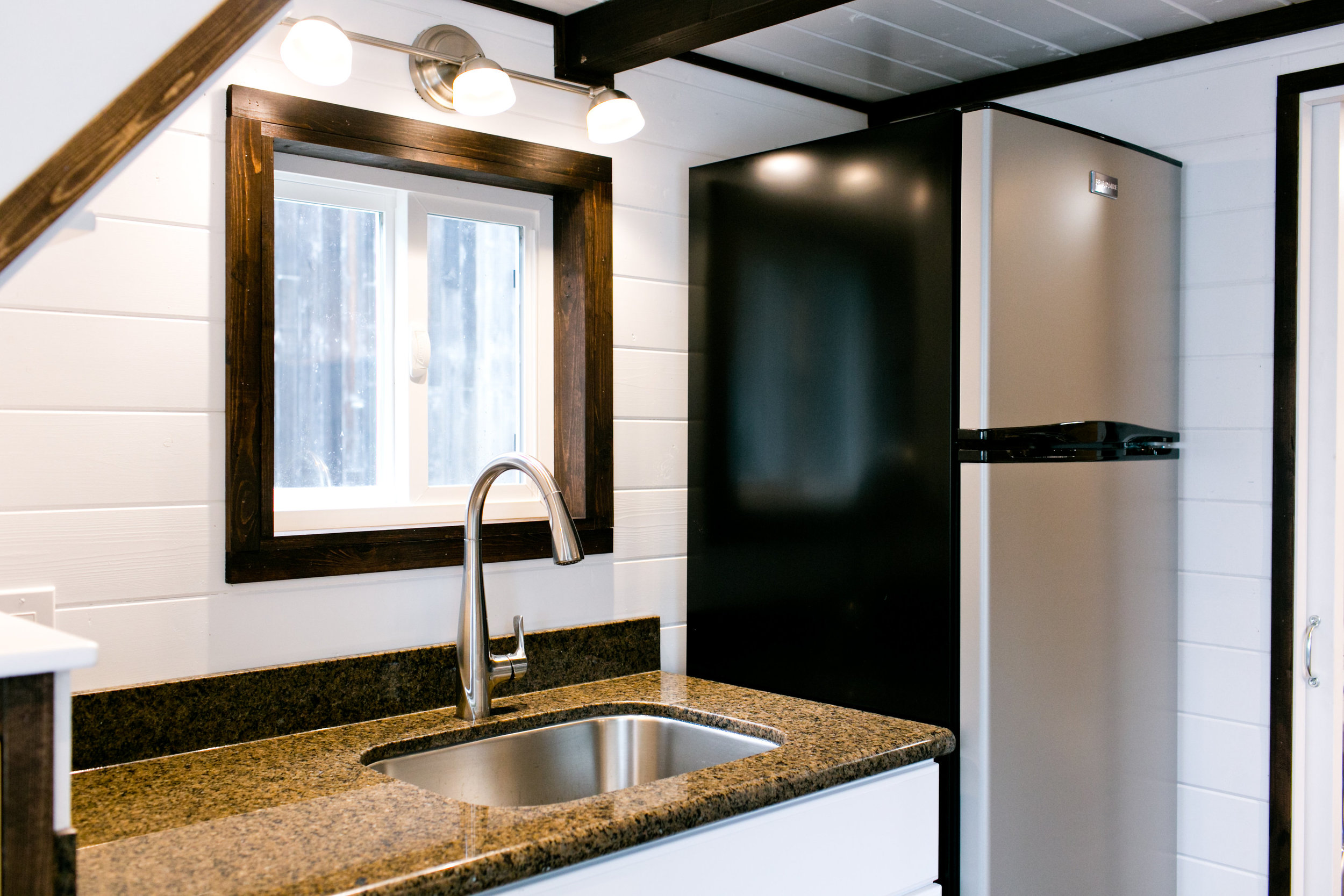 Galley kitchen features sink opposite the stove