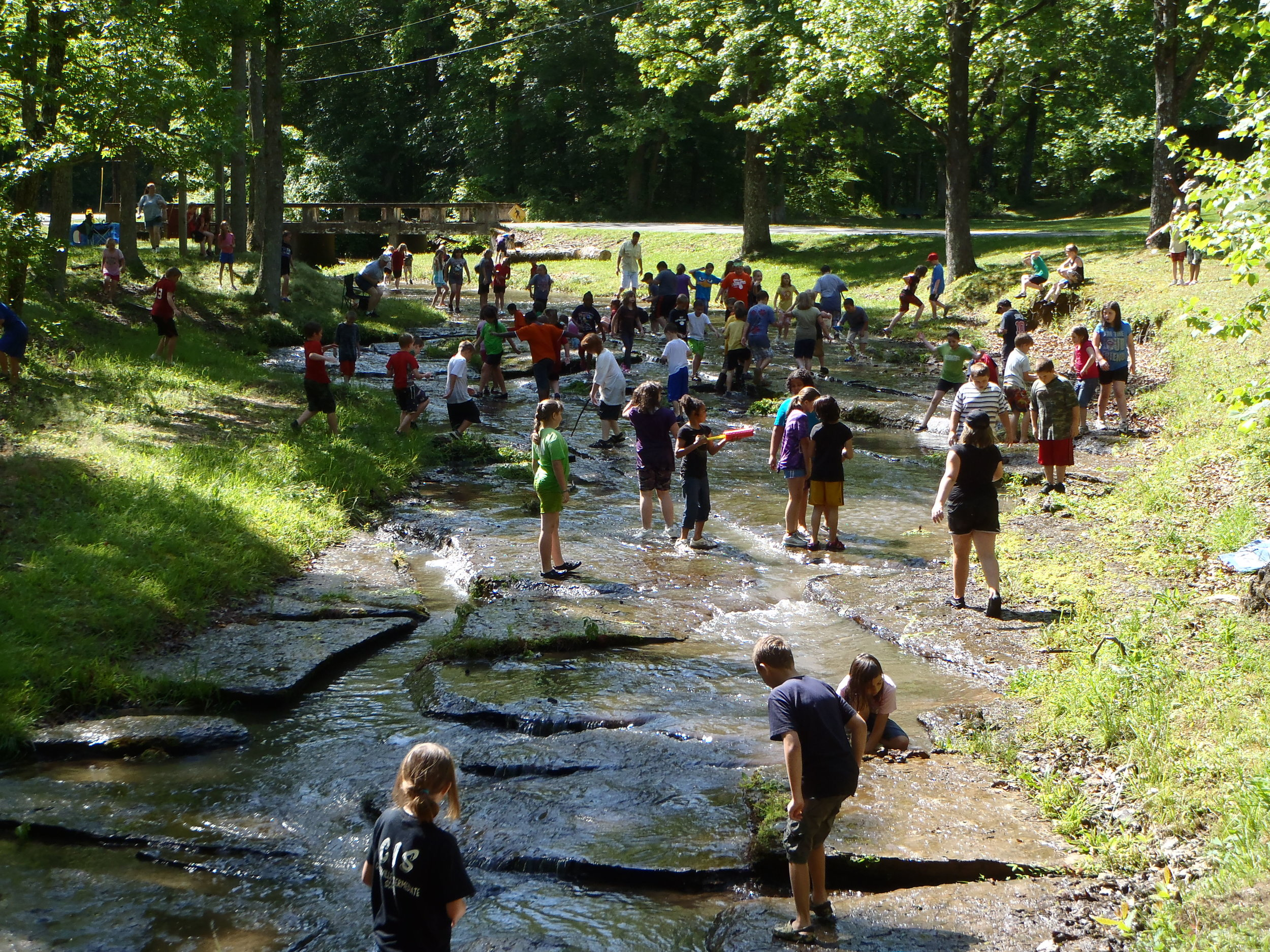 Lots of Summer Campers in a shallow part of a creek staying cool - NaCoMe Camp & Conference Center