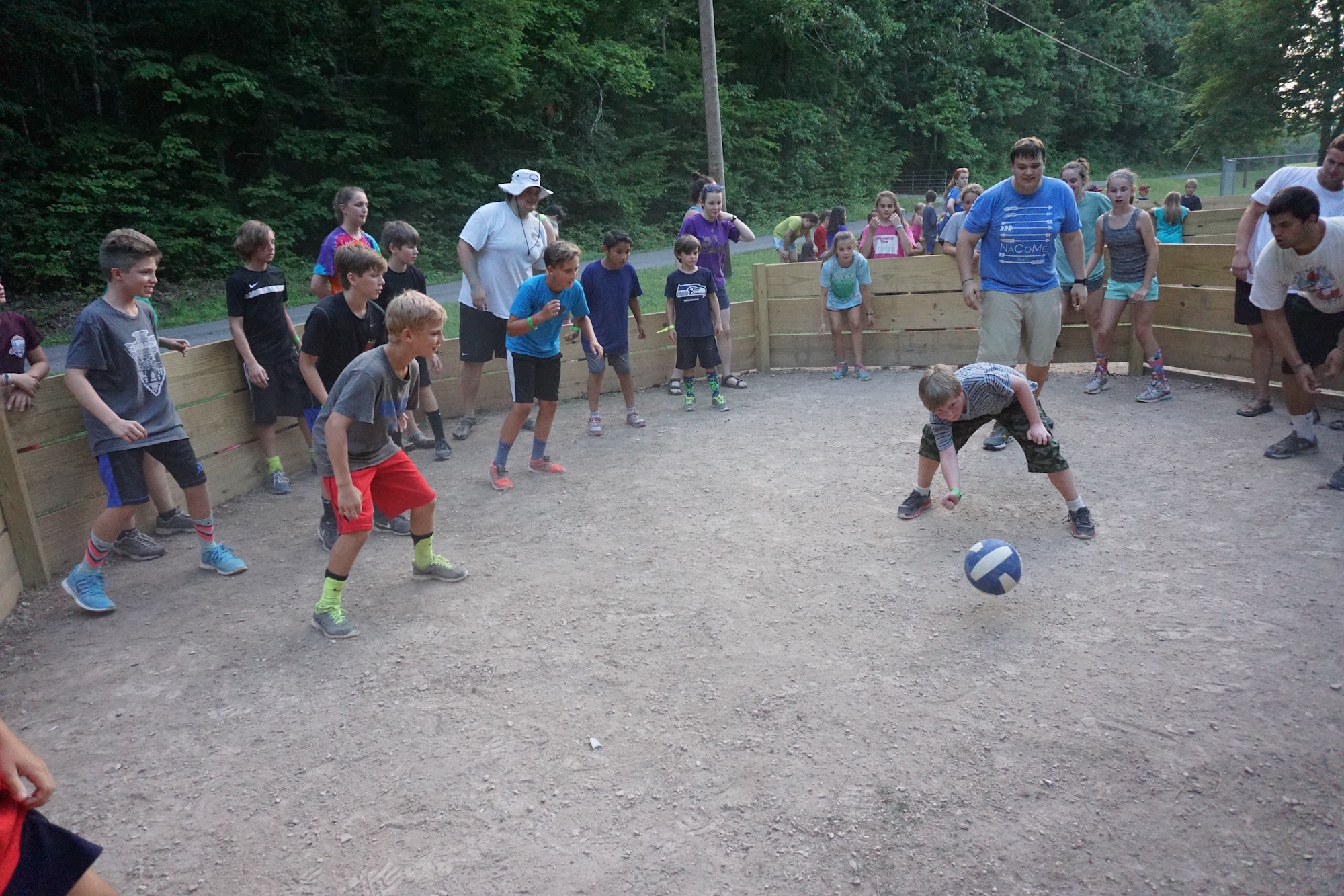 A circle of Summer Campers playing a game with a ball - NaCoMe Camp & Conference Center