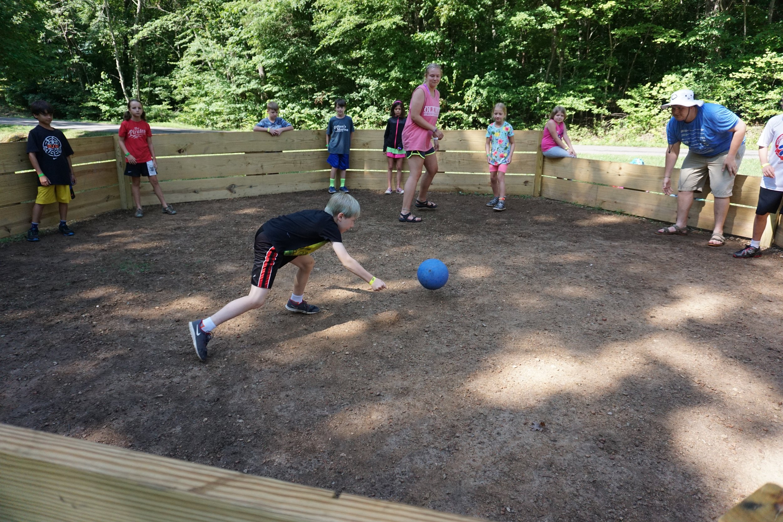 An intergenerational group of Summer Campers playing ball in a circle - NaCoMe Camp & Conference Center
