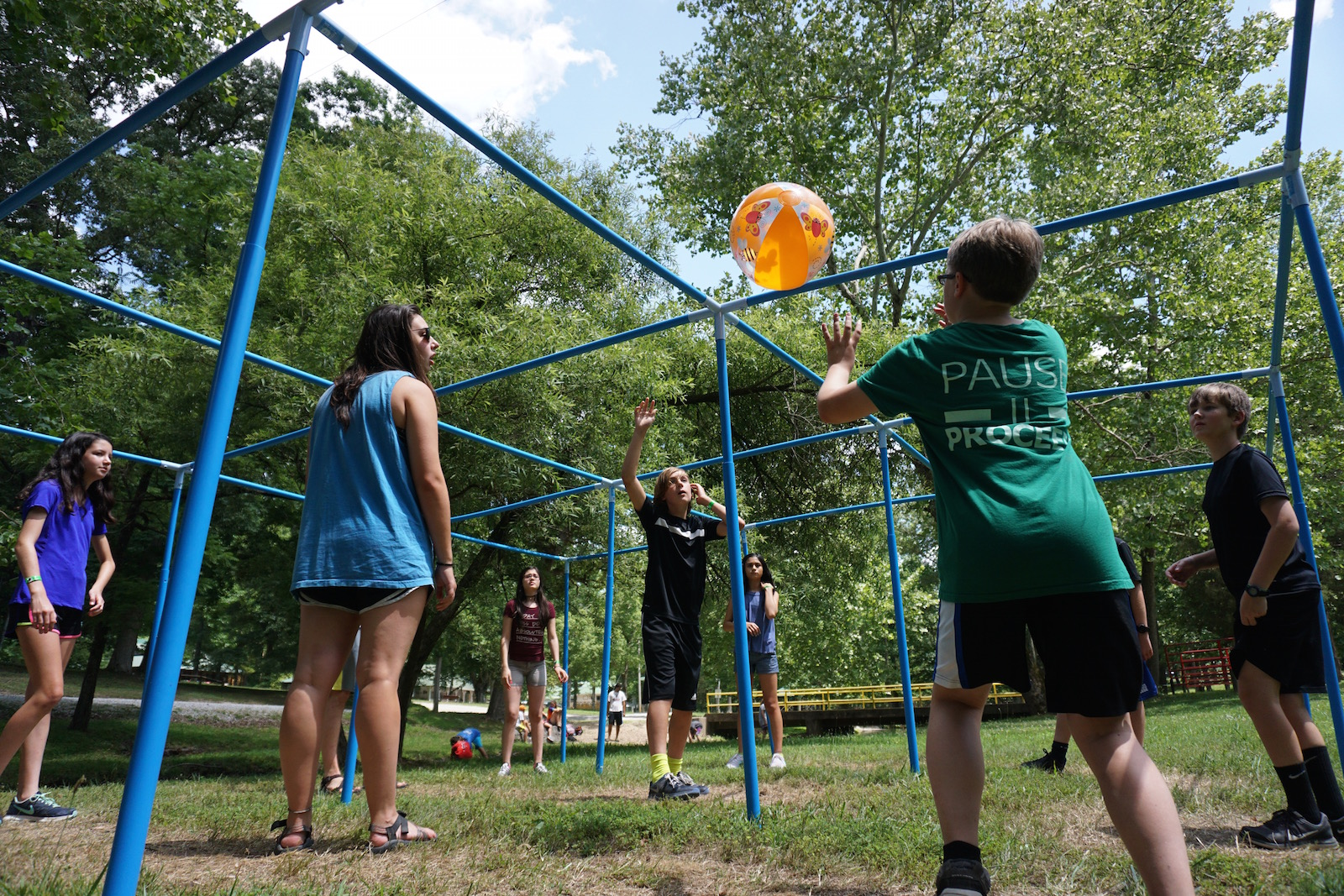 Middle School aged Summer Campers playing a game with an orange ball - NaCoMe Camp & Conference Center