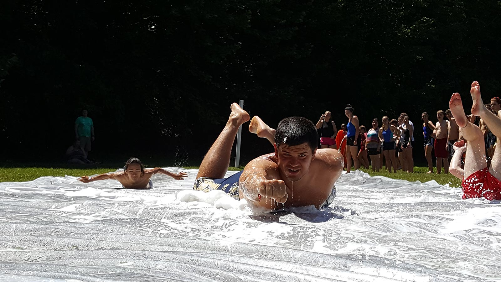 Teenager or camp counselor and young Asian boy sliding on their stomach on a homemade slip & slide - NaCoMe Camp & Conference Center