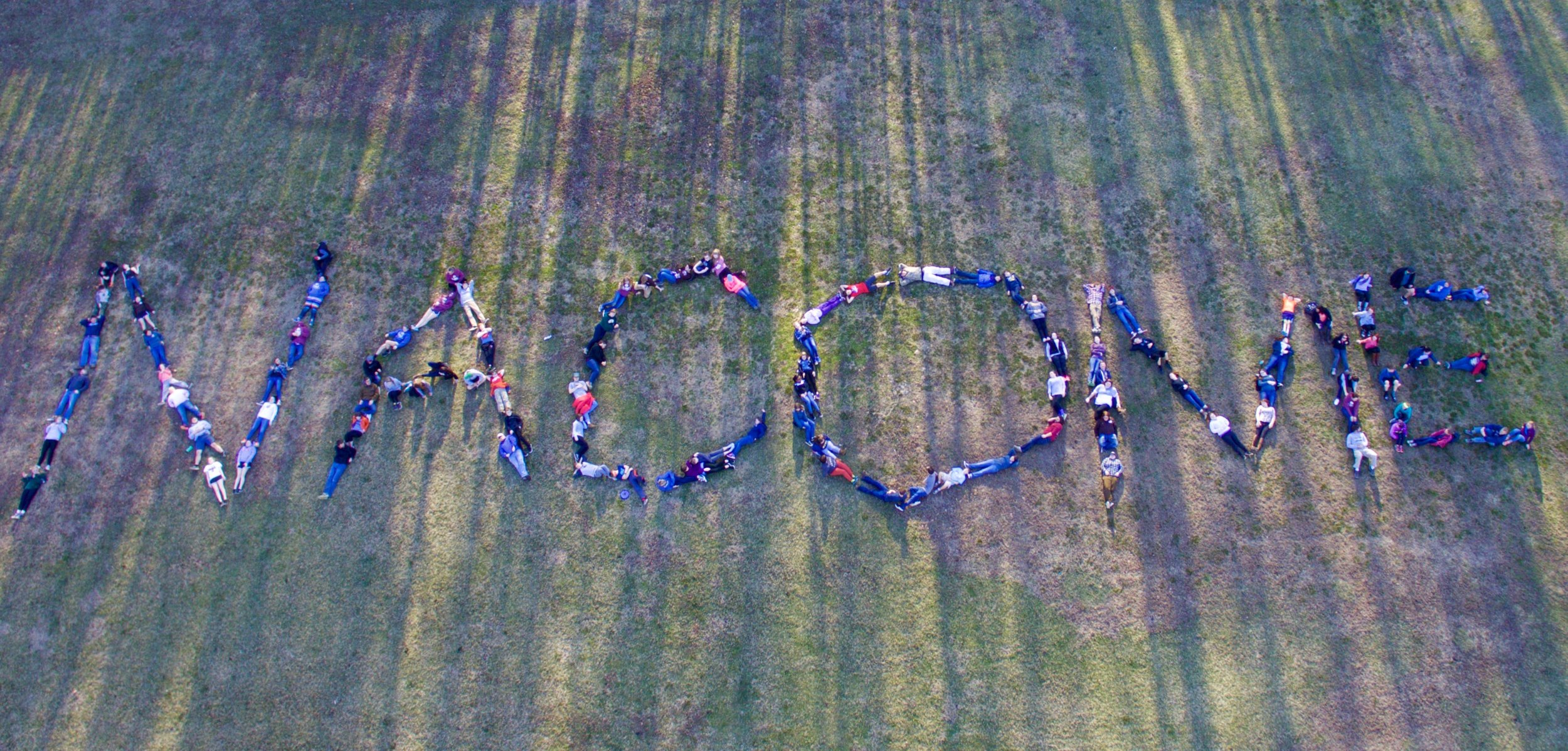 NaCoMe campers youth from above drone spelling camp name- NaCoMe Camp and Retreat Center