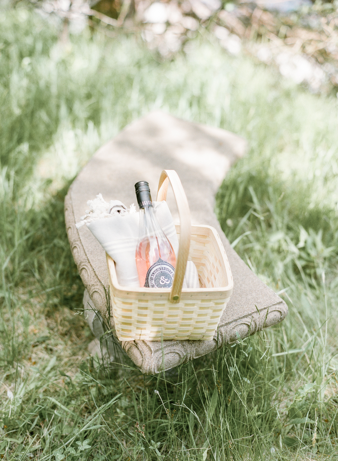 Jacqueline Anne Photography Captured on Film, A cream sunhat on a sunny bench, with a bottle of Lightfoot and Wolfville Wine