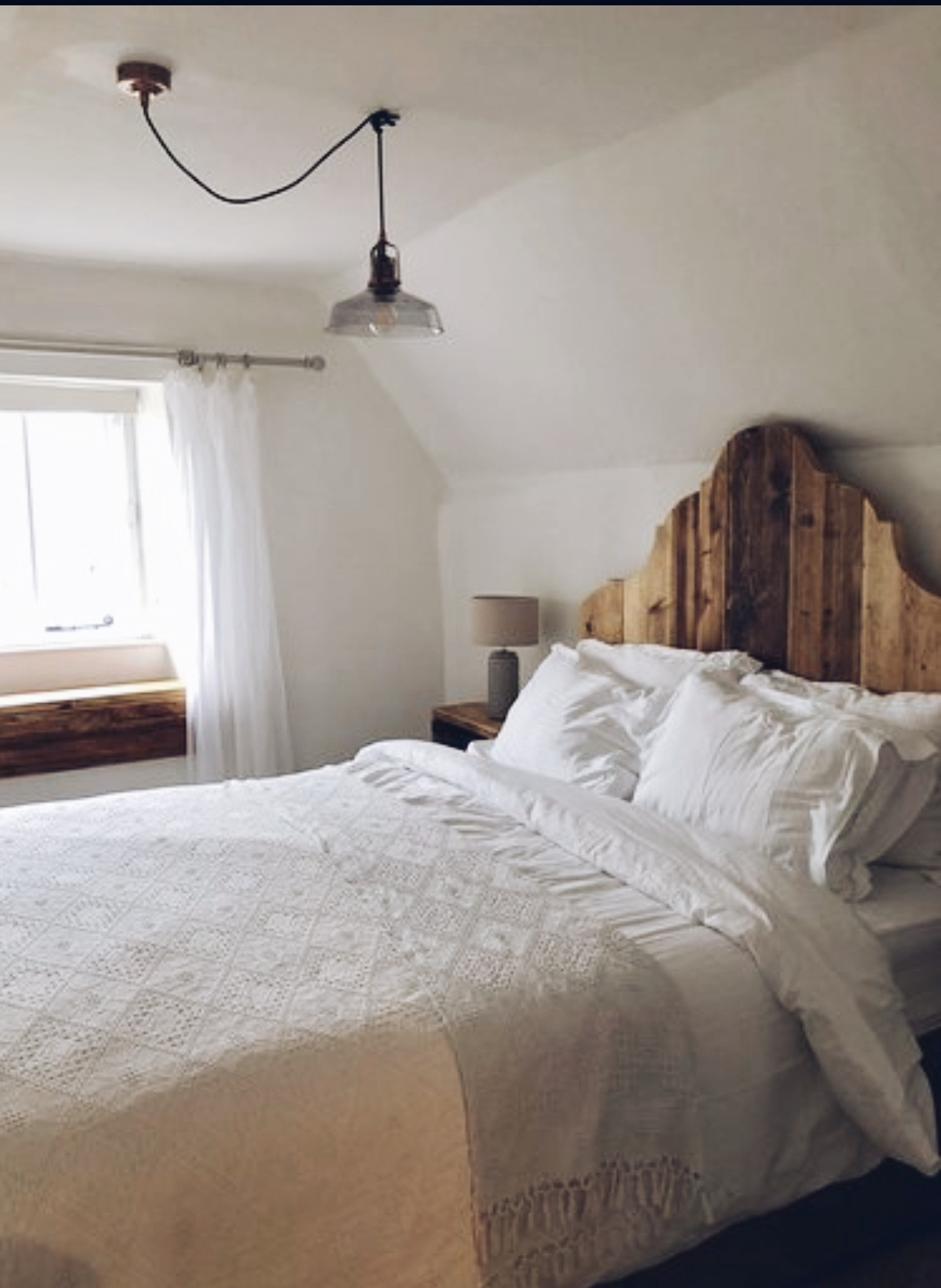 The master bedroom at  Bee Cottage  with a fabulous reclaimed wood headboard