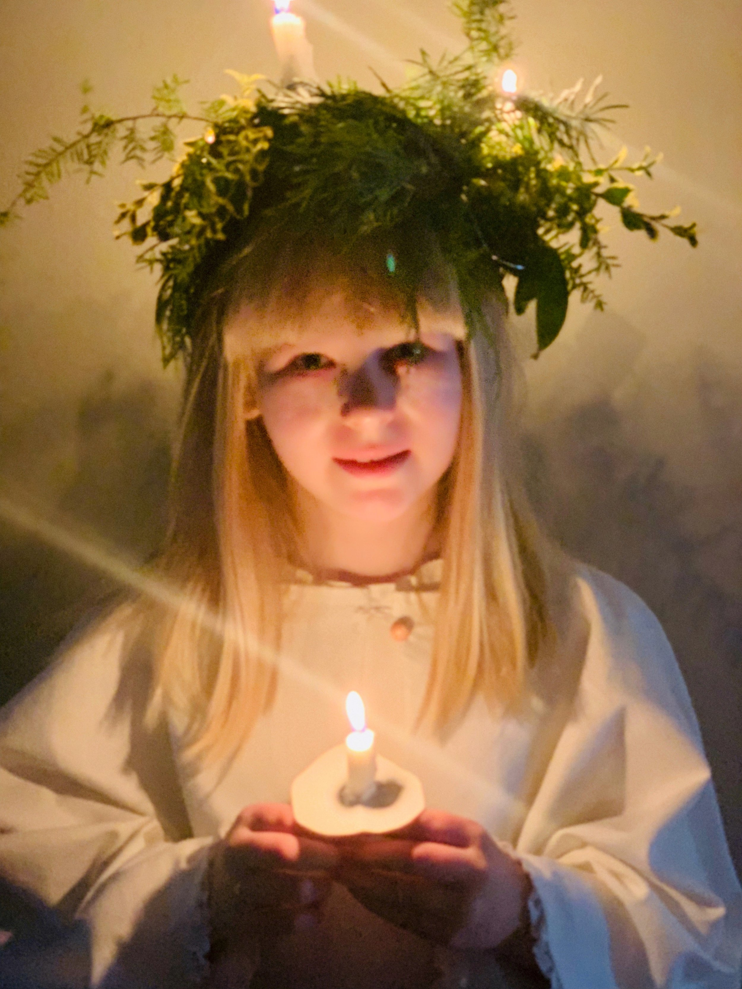 The oldest second grade girl wears a wreath of lit candles, representing Santa Lucia.