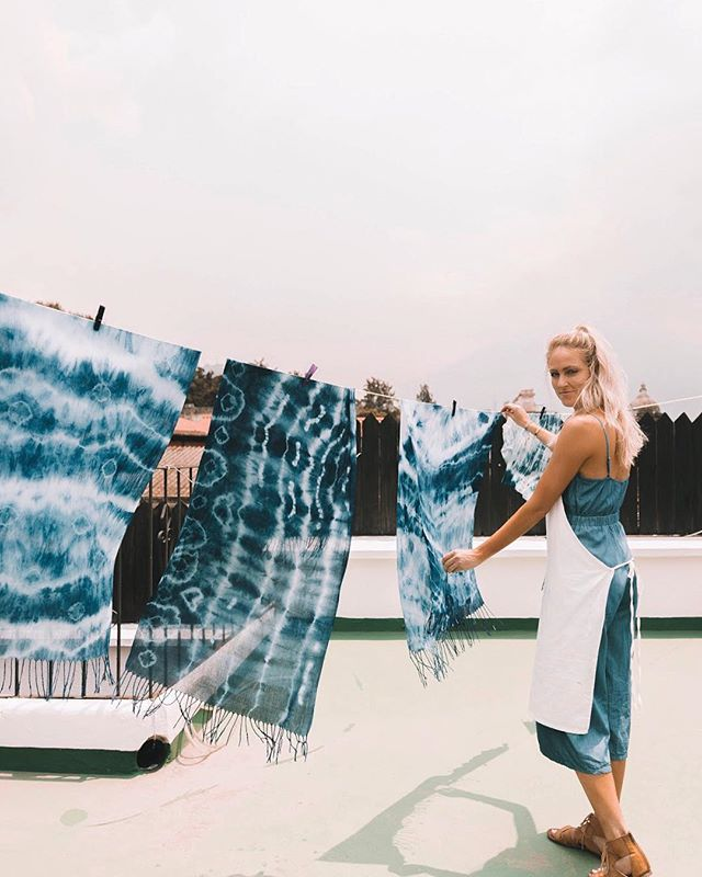 "INDIGO dyeing with the ""godmother of natural dyes in Guatemala,"" Olga Reiche.  Olga is a local legend. After the earthquake in 1976, she partnered with the government to travel throughout the country, interviewing artisans and making sustainability recommendations.  Today, Olga has invested over thirty years experimenting with dyeing techniques and she continues to lead the way in sustainability, utilizing materials like corn husks, plastic bags, cassette tapes, and jeans to create products for her own line of naturally dyed and recycled products.  This week, we were the first official class on the rooftop of her shop in town, Indigo. We learned the basics of shibori-inspired to create patterns with indigo dye and learned how to set up the vat. Thank you, @stela_9 for introducing us to another woman warrior and entrepreneur!  Photo: @britt_ellison"