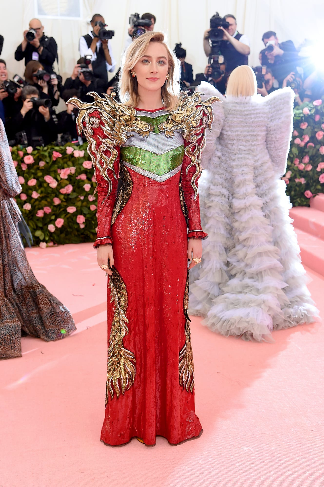 - Yes, Gucci is always a wise choice for being campy.Saorise Ronan in this bright red sequinned gown featuring golden-flame shoulders. Although I can't deny the dress is quite sensational, I wish I could see a more outraging makeup look or head piece.