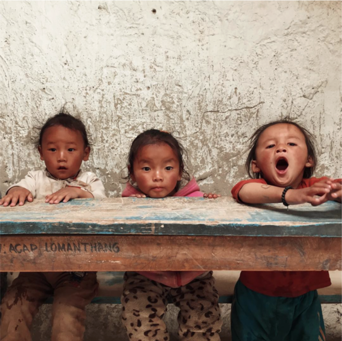 """Namgyal (2/2):  2) There are less than ten students at the school in Namgyal. They all squeeze onto two benches in a room with nothing but a chalkboard and a few torn posters on the wall. The school houses toddlers and teenagers, but only one """"curriculum."""" When we arrived, the oldest kid was reciting the alphabet and the younger ones were echoing her, chanting in unison.  Lhakpa, a teacher and member of our volunteer team (who grew up in a village not far from Namgyal), had a day full of fun activities planned for the kids. She read stories to them. She taught them about proper brushing and hand-washing techniques. And when she brought out paintbrushes and watercolors, they were overjoyed. Most of them had never seen paint before!  I still can't wrap my head around the fact that had I been born a generation earlier, I would probably be living in a village and attending a school just like the one in Namgyal. Instead, I live thousands of miles away in one of the most technologically advanced places in the world, and I get to study at a prestigious global university. I am so, so lucky. Chances are, if you're reading this, you've probably also had the privilege of studying at a school that's not limited to a single room and rote memorization. We are so, so lucky. And I think we tend to forget that way more often than we should. My parents always tell me to put my education before anything else, advice I've neither gone against nor truly adhered to. I've skipped my fair share of classes in the past and I probably will sleep through a few morning lectures in the future. But I'm trying to acknowledge my luck and pay a little bit of it forward, in hopes that some of it will make its way to the kids in Namgyal."""