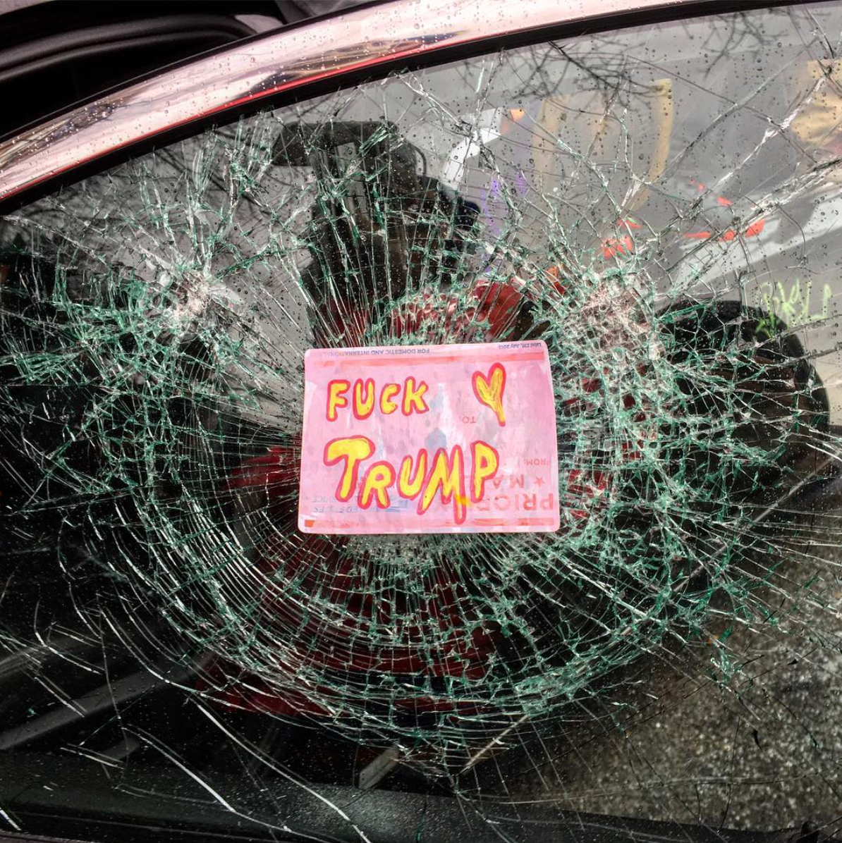 Anti- #Trump  protestors smashed and decorated the window of a parked limousine on  #InaugurationDay . Washington, D.C.