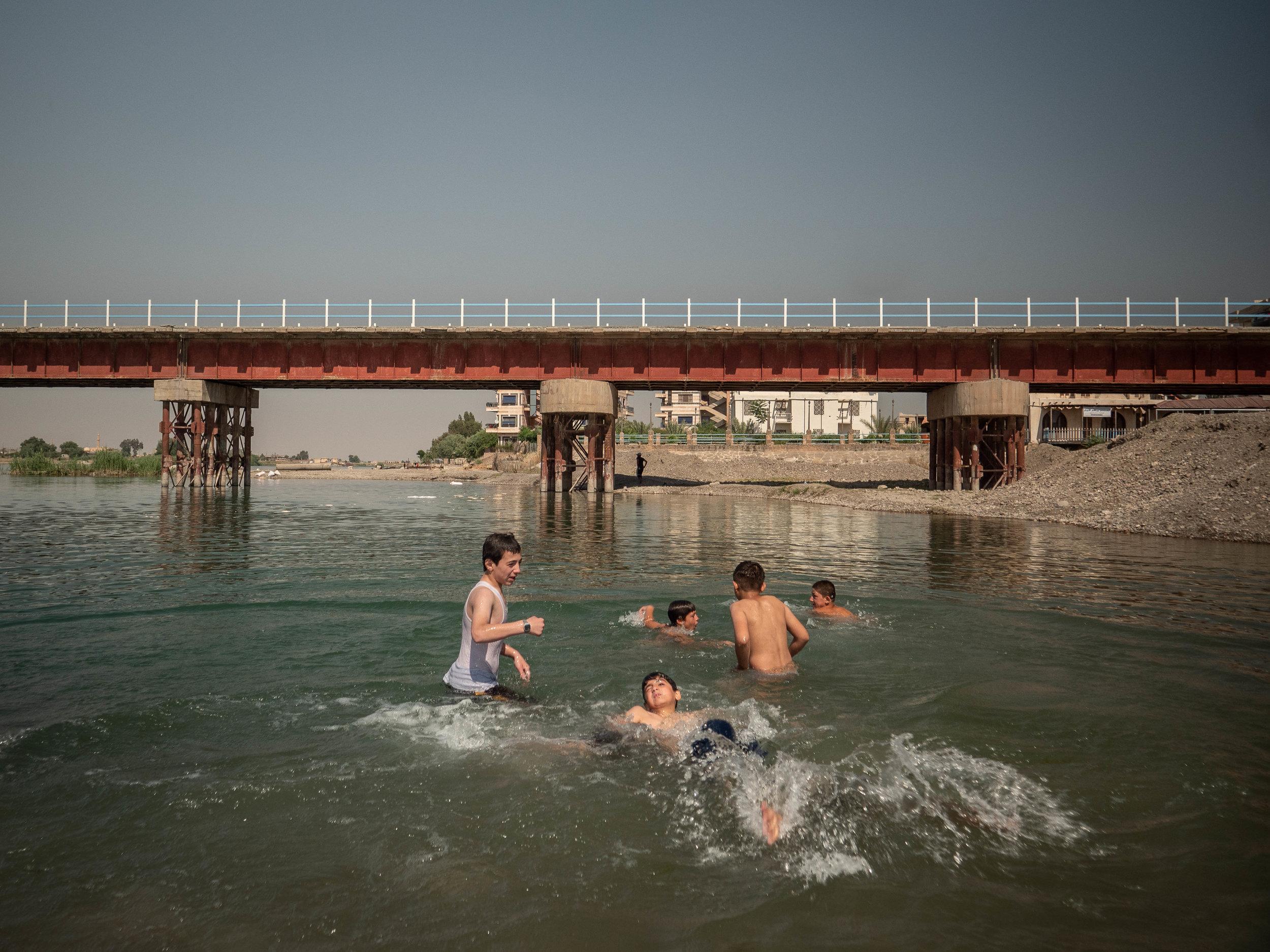 29/05/19, Raqqa, Syria - A group of boys swim in the Euphrates river in Raqqa.