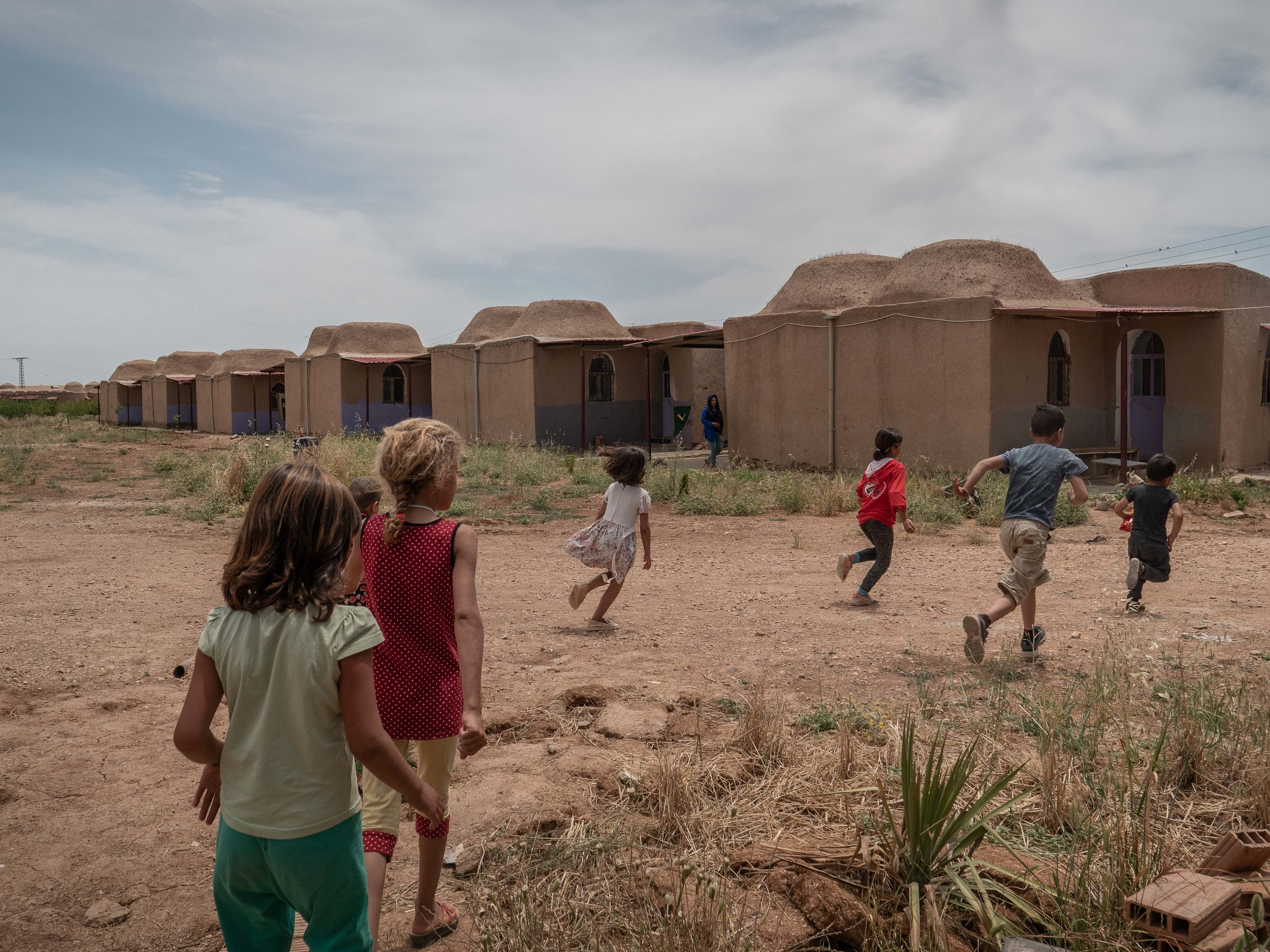 31/05/19, Jinwar, Syria - Children run in front of some traditional houses in the women village of Jinwar.