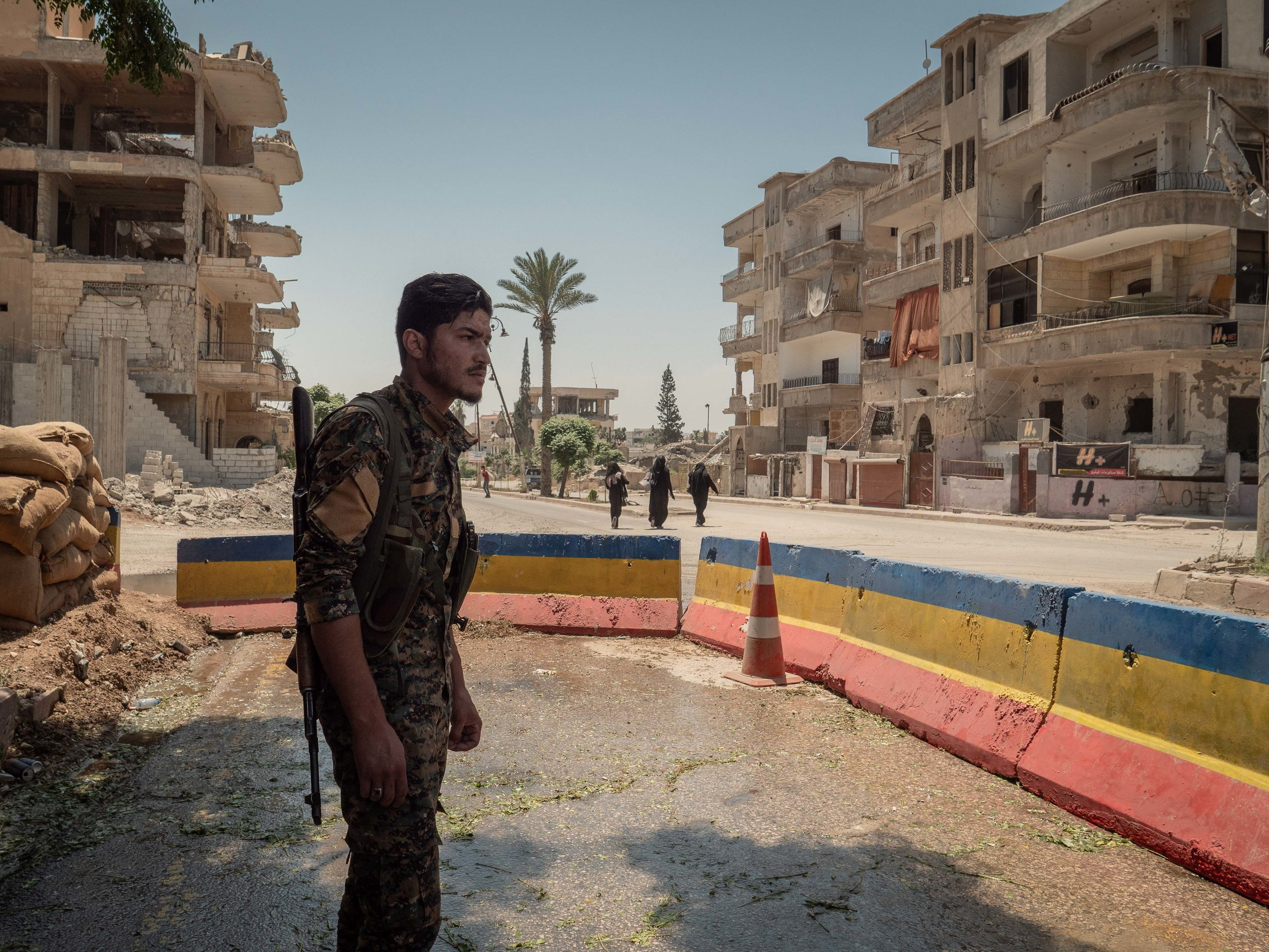 29/05/19, Raqqa, Syria - A member of the security forces patrols the headquarter in Raqqa near the site of a suicide attack.
