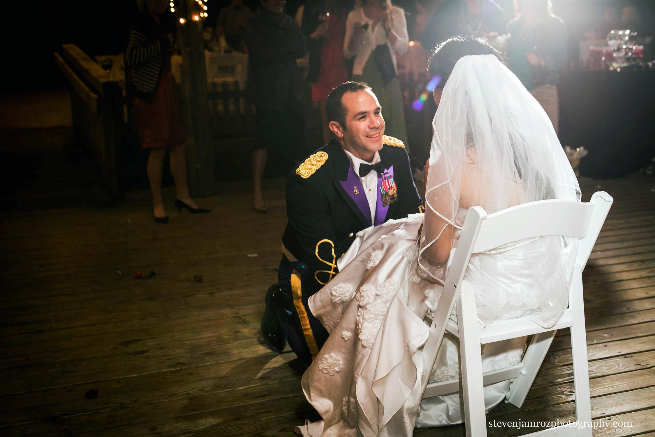 groom-on-knee-taking-off-garter-wedding-raleigh-0944.jpg