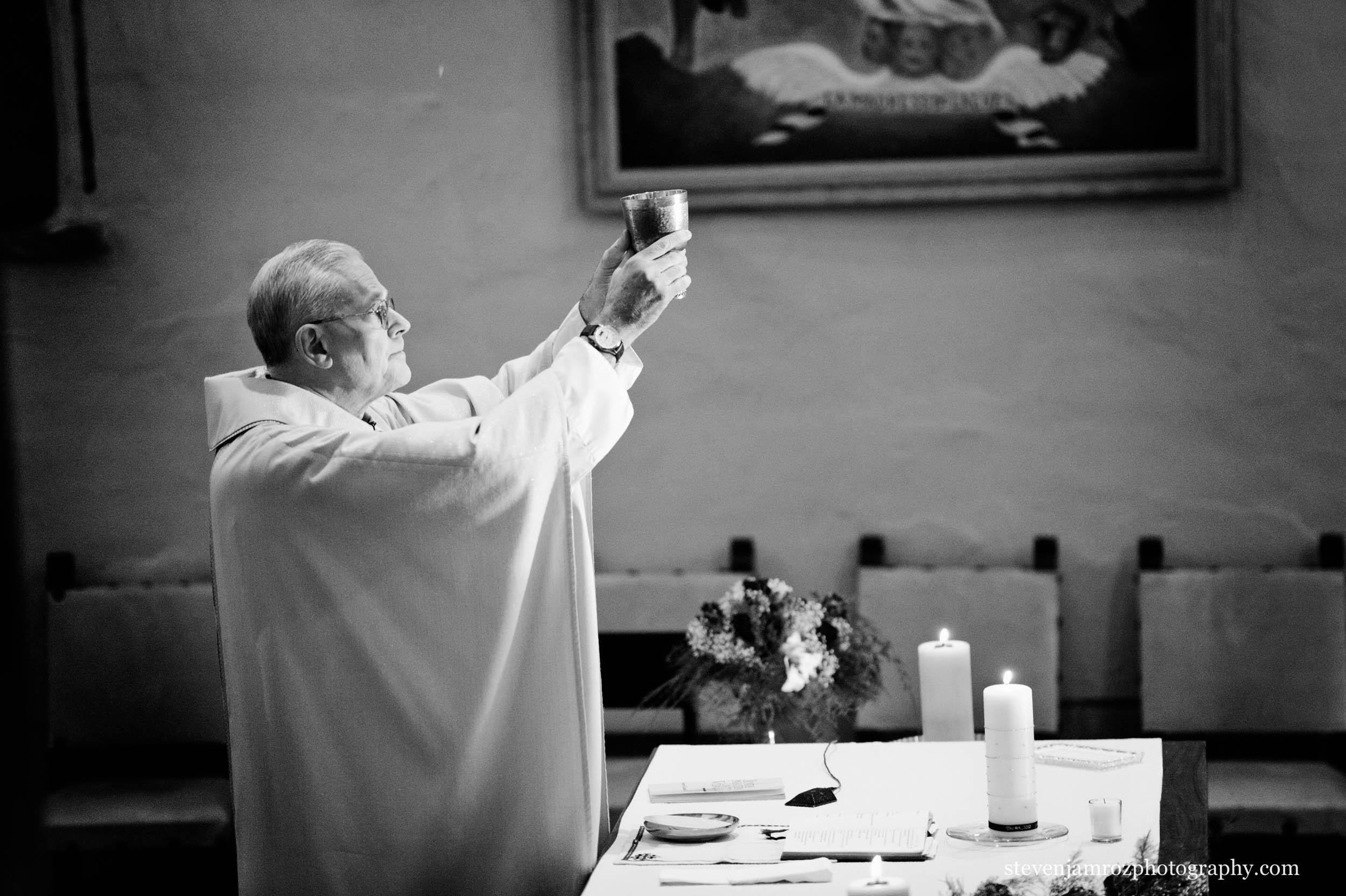 priest-holds-wine-durham-nc-wedding-steven-jamroz-photography-0444.jpg