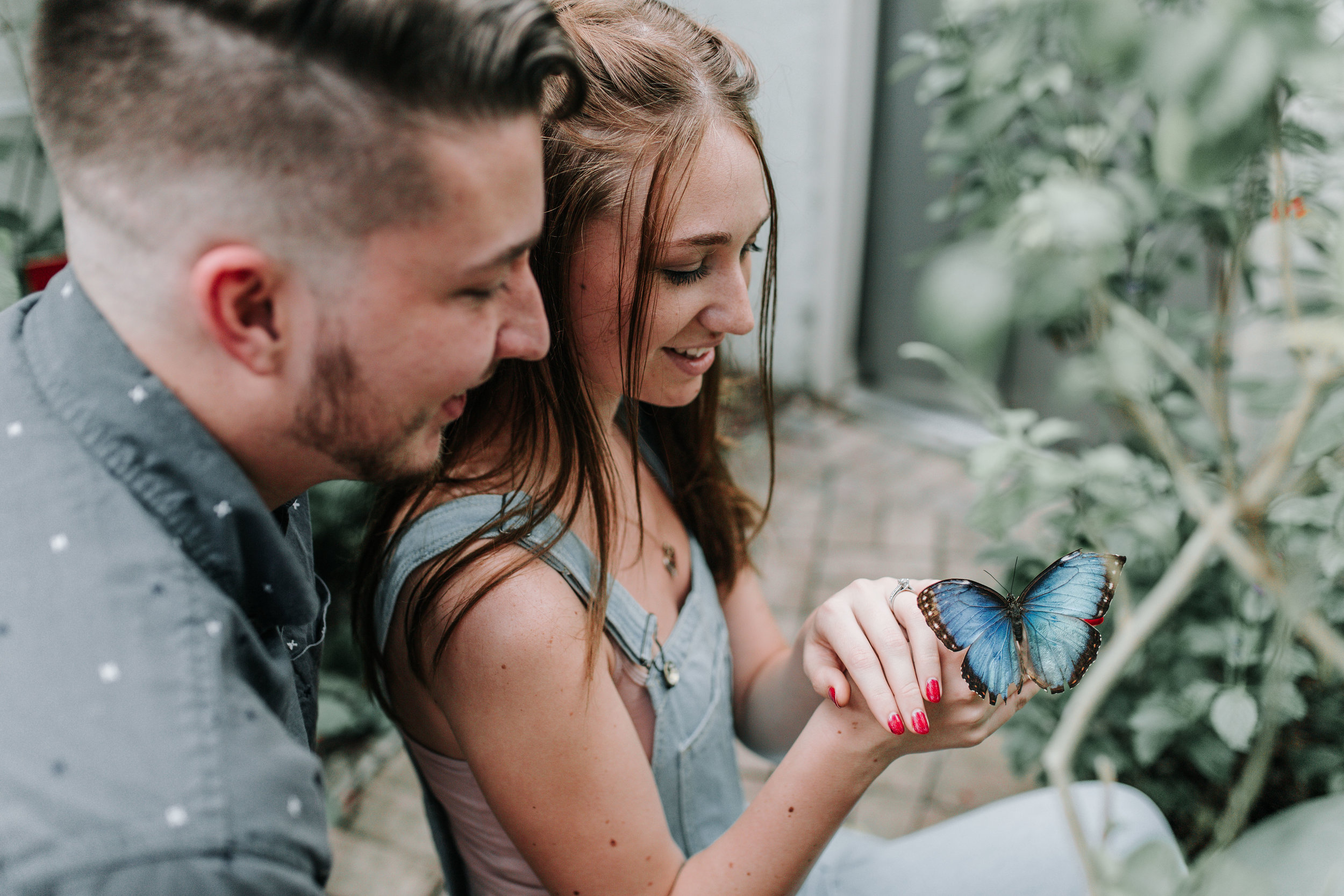 Couple holding butterfly during engagement session