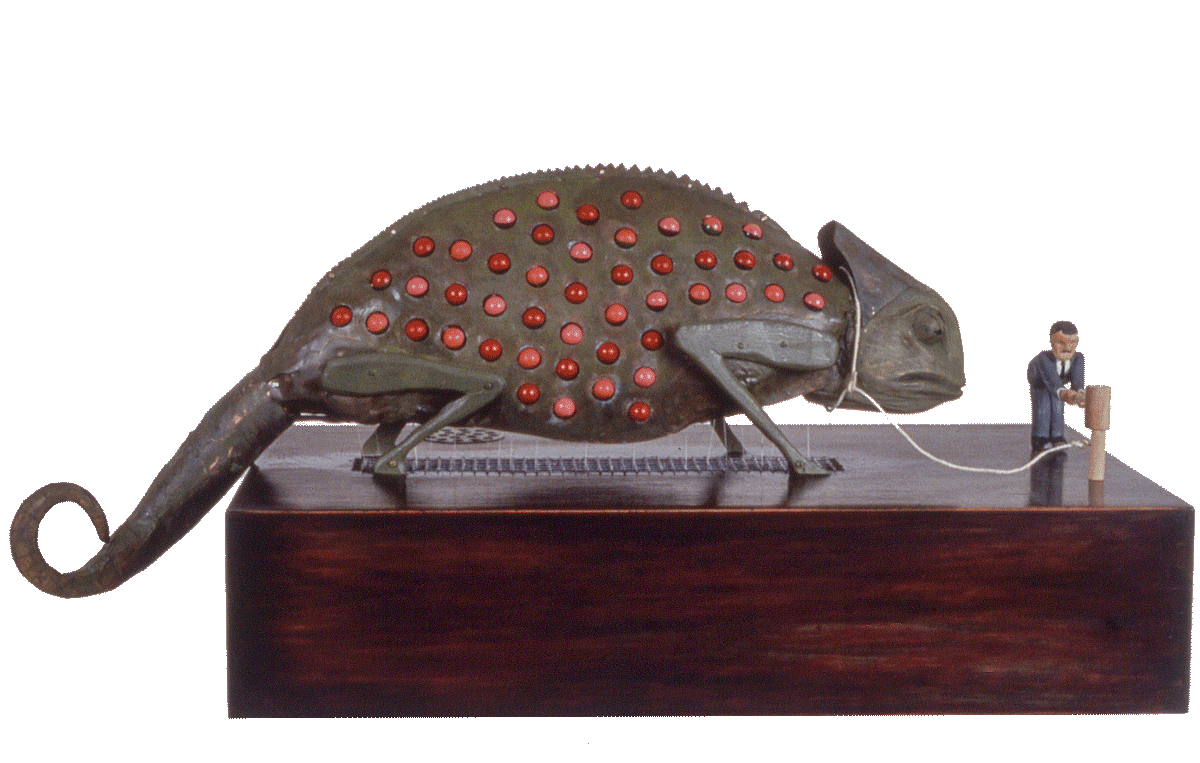 Chameleon,  copper, electric motor, painted beads, wood. Beads were half-painted; an intricate system of levers and pulleys moved the beads in a preset pattern while the man occasionally pounded the restraining 'stake.' Far too complex to function for very long, the copper quickly corroded and sealed the beads in place.