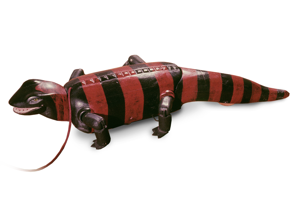 Komodo (pull toy),  carved and painted wood with pull cord. When pulled the jaws snap, feet move, and tail moves side to side… but mainly it's a gorgeous paint job. More Gila Monster than dragon.