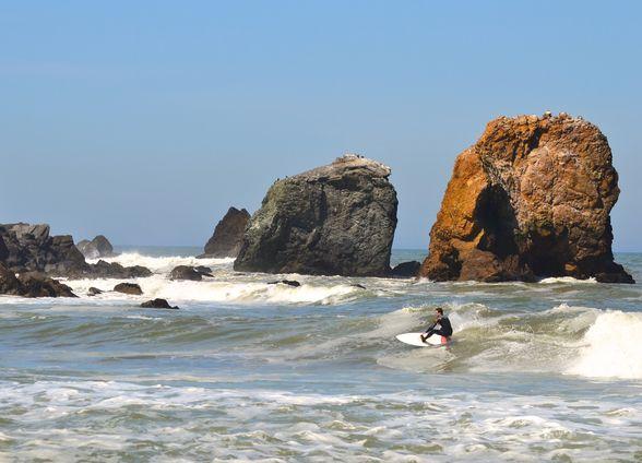A surfer at Rockaway Beach (©Visit Pacifica)