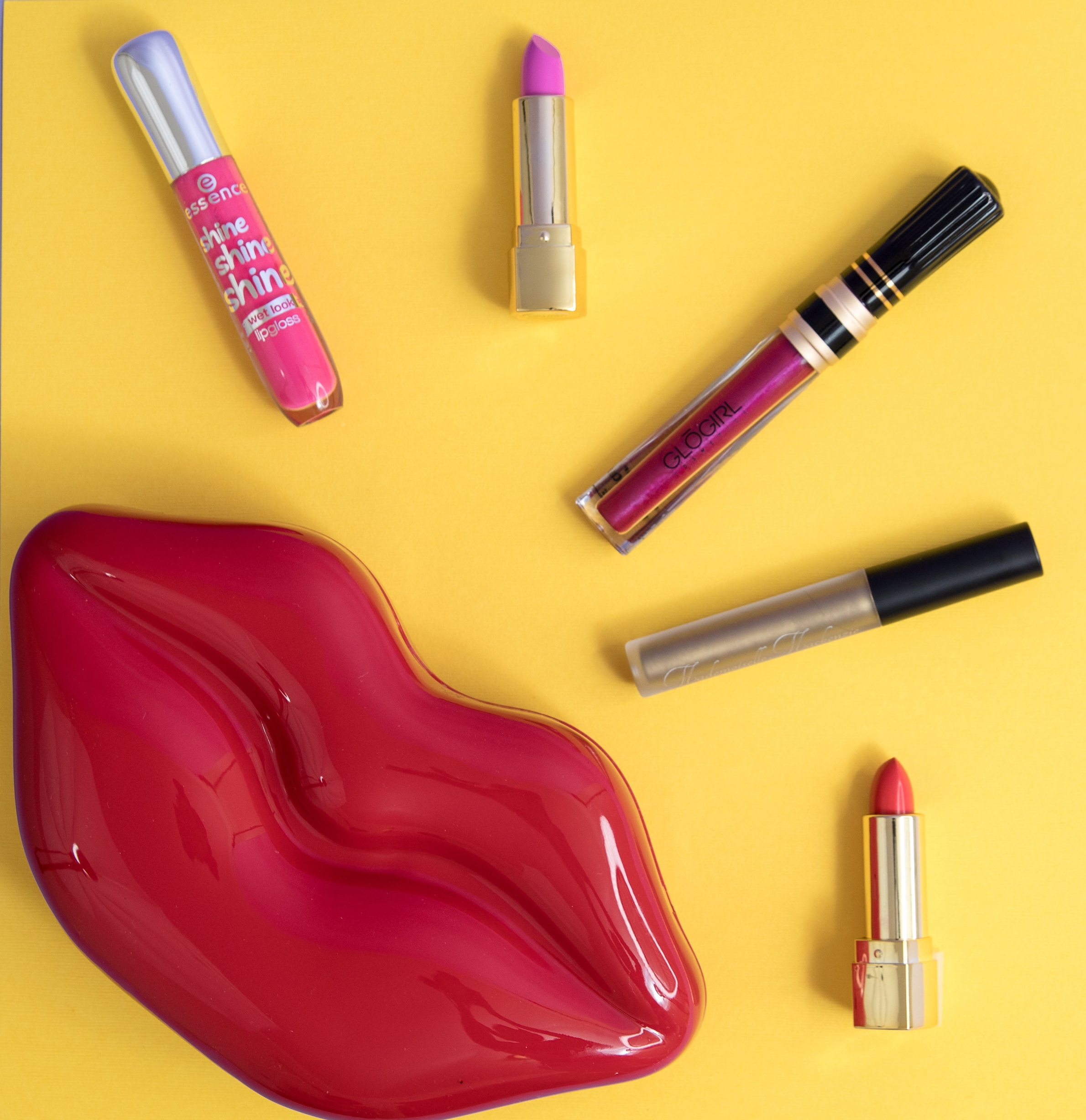"Lipsticks come in a rainbow of shades, perfect for Spring 2018! Check out our favorites (from left to right:  Essence Shine Shine Shine Lipgloss  in ""Flirt Alert,"" GloGirl Cosmetics Lipstick in "" Hella Pink ,"" GloGirl Cosmetics Lip Drips in "" Pimp Juice ,""Mademoiselle Mackenzie Bold Liquid Lipstick - Metallic Edition in "" Tarnished Gold ,""GloGirl Cosmetics Lipstick in  "" Lucille ."""