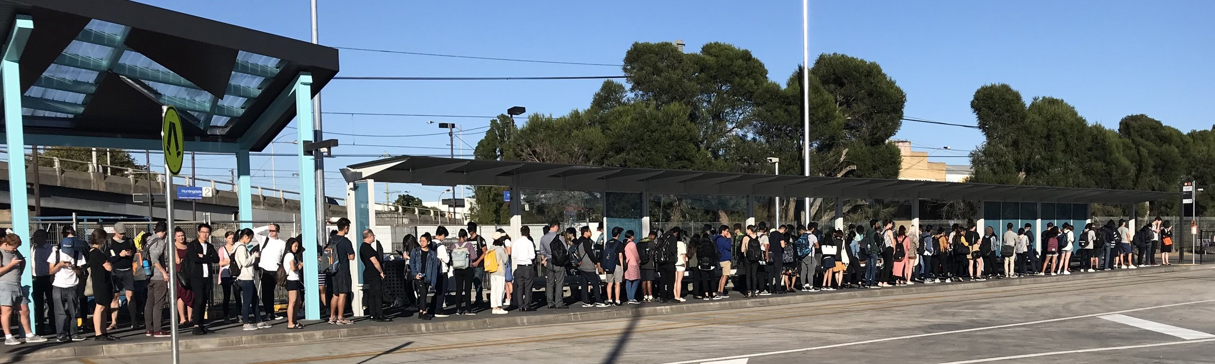 Around four busloads of passengers (the line had doubled back, and stretches out of frame) await the  601 Monash Express Shuttle .