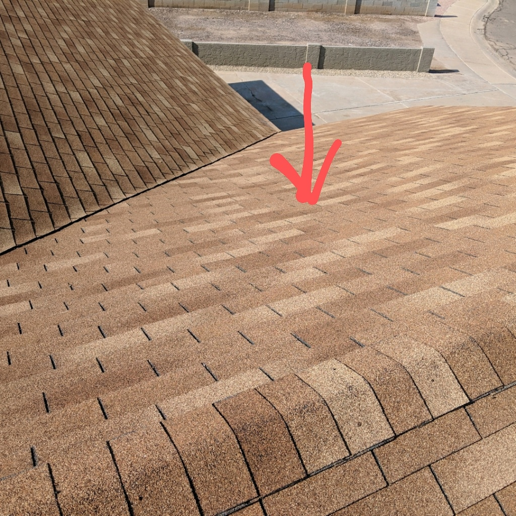 Low/soft spots in roof deck indicate rotting sheathing and can be unsafe to walk on. New sheathing must be installed during the next re-roof.