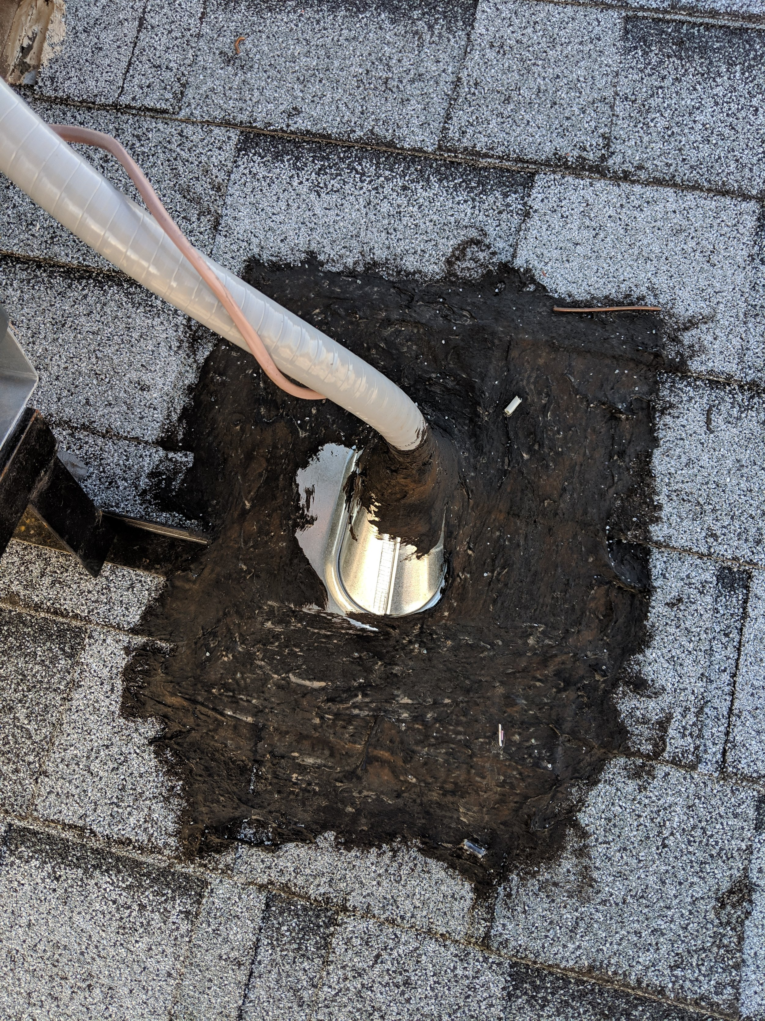 Roof flashing around electrical conduit to heat pump was completely covered with tar. This is not the work of a professional roofer and should be repaired.