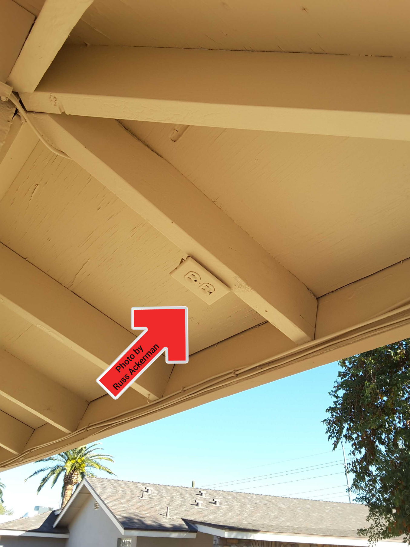 This receptacle may be under the eaves, however it should still be a weather resistant receptacle with a cover and GFCI protected.